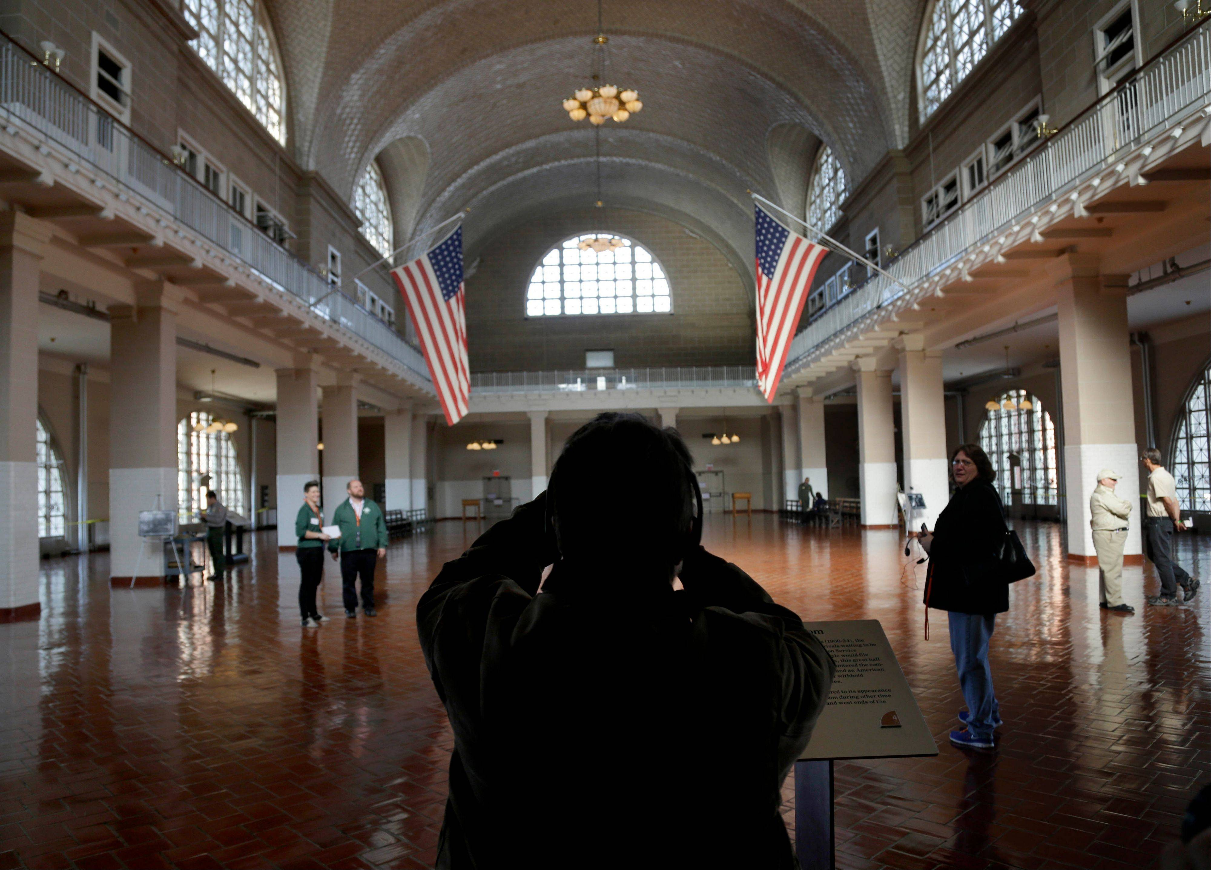 A visitor to the newly re-opened Ellis Island stops to take a picture of the registry room in New York on Monday. The island that ushered millions of immigrants into the United States received visitors Monday for the first time since Superstorm Sandy. Sandy swamped boilers and electrical systems and left the 27.5-acre island without power for months.