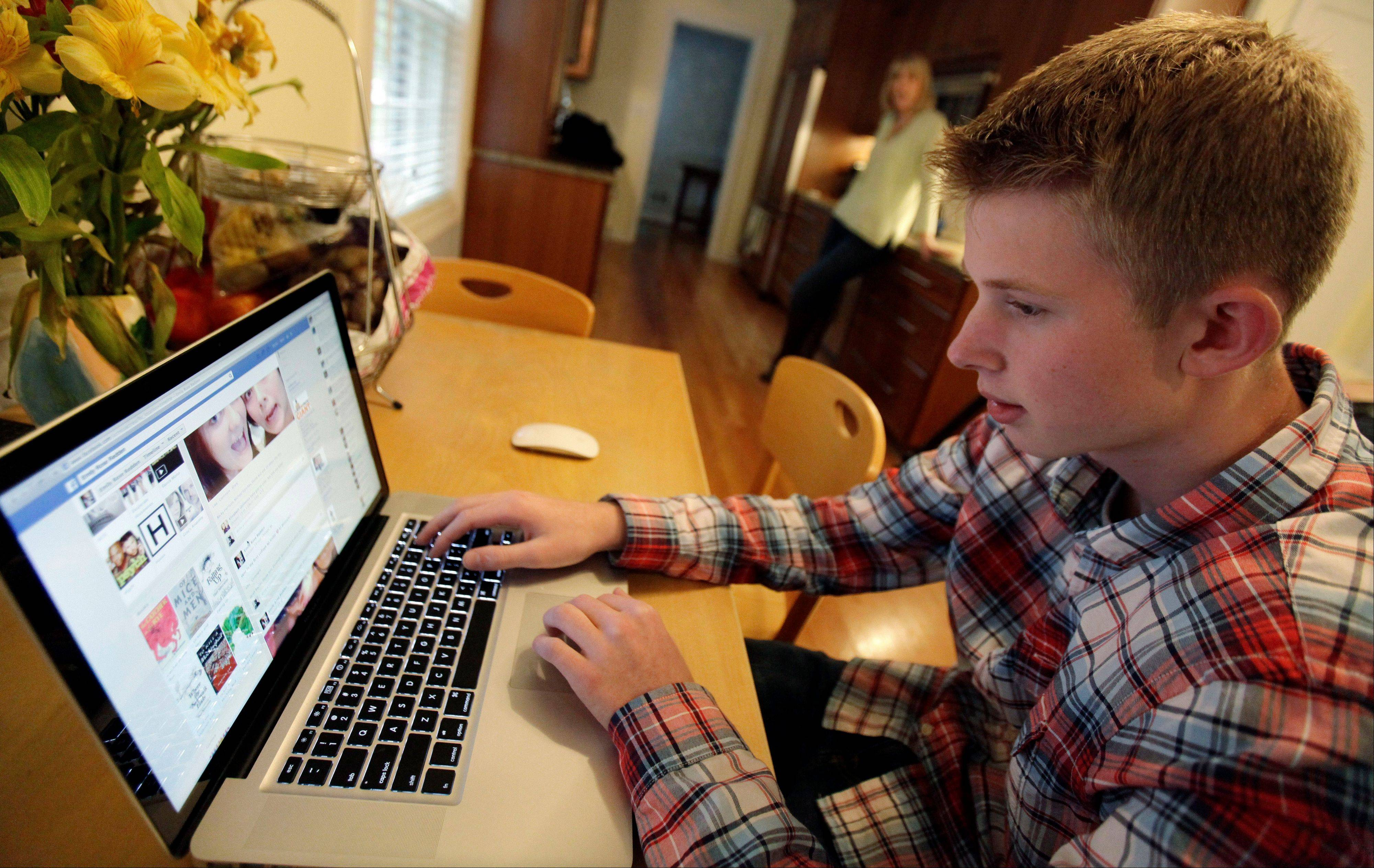 Associated PressMark Risinger, 16, checks his Facebook page on his computer as his mother, Amy Risinger, looks on at their home in Glenview.