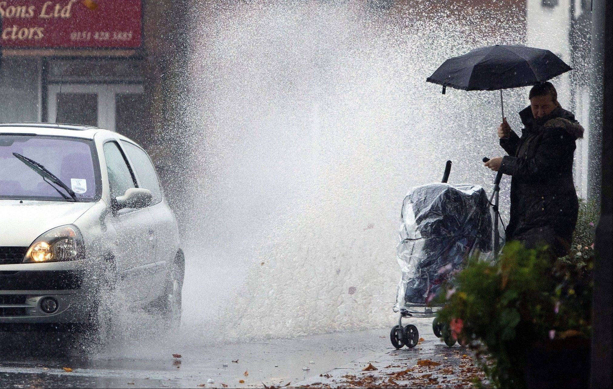 A lady with a child in a pram turns from the oncoming deluge from a passing car in Liverpool, England, after heavy rain fell over the country Monday.