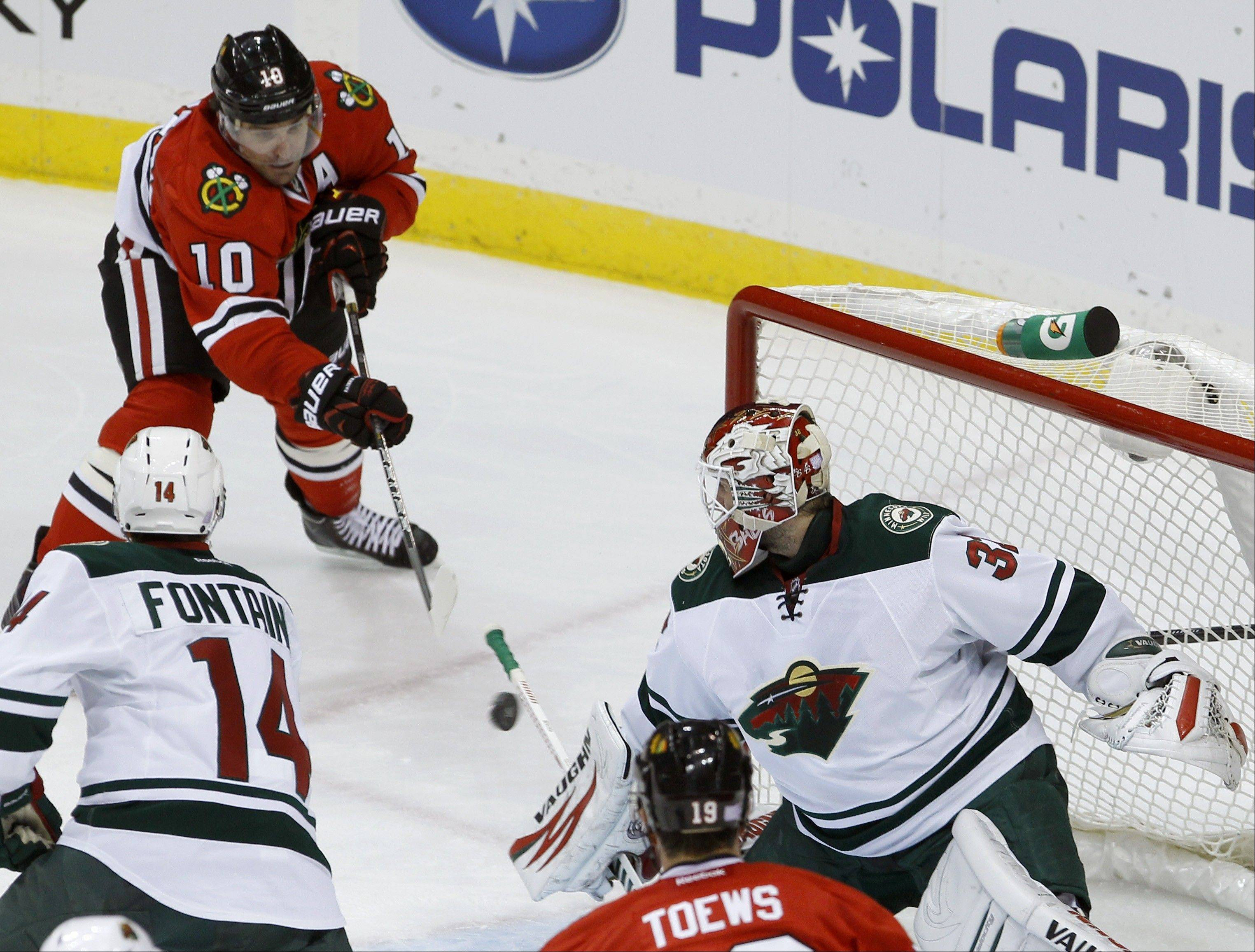 Chicago Blackhawks center Patrick Sharp (10) scores on Minnesota Wild goalie Niklas Backstrom (32) of Finland during the first period of an NHL hockey game in St. Paul , Minn., Monday, Oct. 28, 2013.