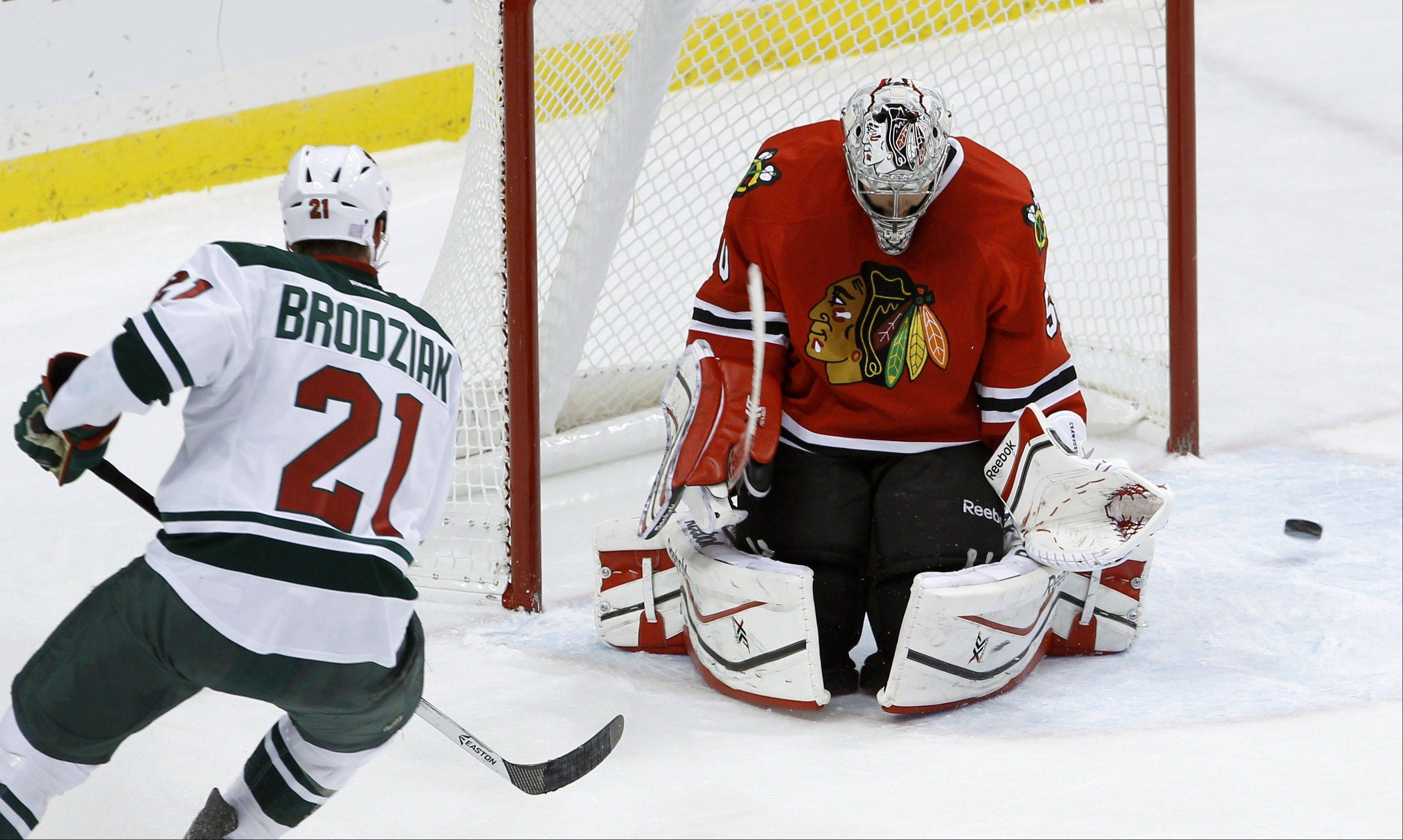 Chicago Blackhawks goalie Corey Crawford, right, deflects a shot by Minnesota Wild center Kyle Brodziak (21) during the first period of an NHL hockey game in St. Paul , Minn., Monday, Oct. 28, 2013.