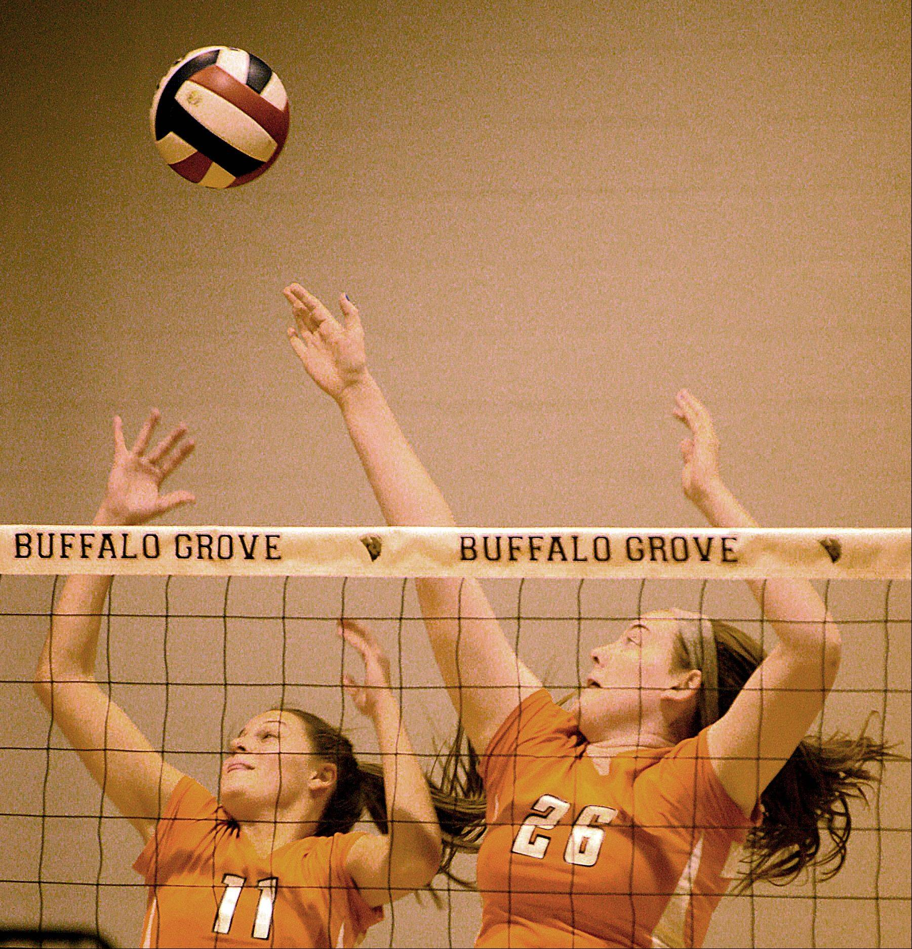Buffalo Grove's Teagan Hutchings, left, and Colleen Nowlan, right, rise up to block the ball during a varsity volleyball game against Deerfield at Buffalo Grove on Monday night.