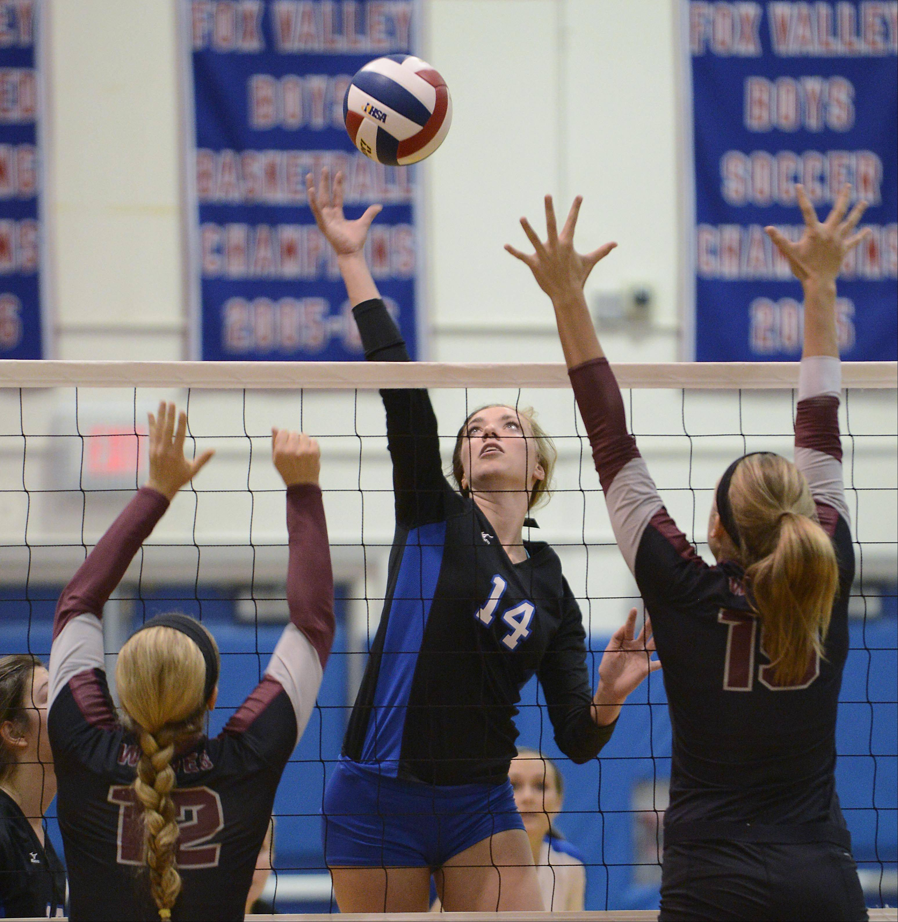Dundee-Crown's Emily Michalski hits to the defense of Prairie Ridge's Charli Beam and Ali Witt, right, Monday in Carpentersville.