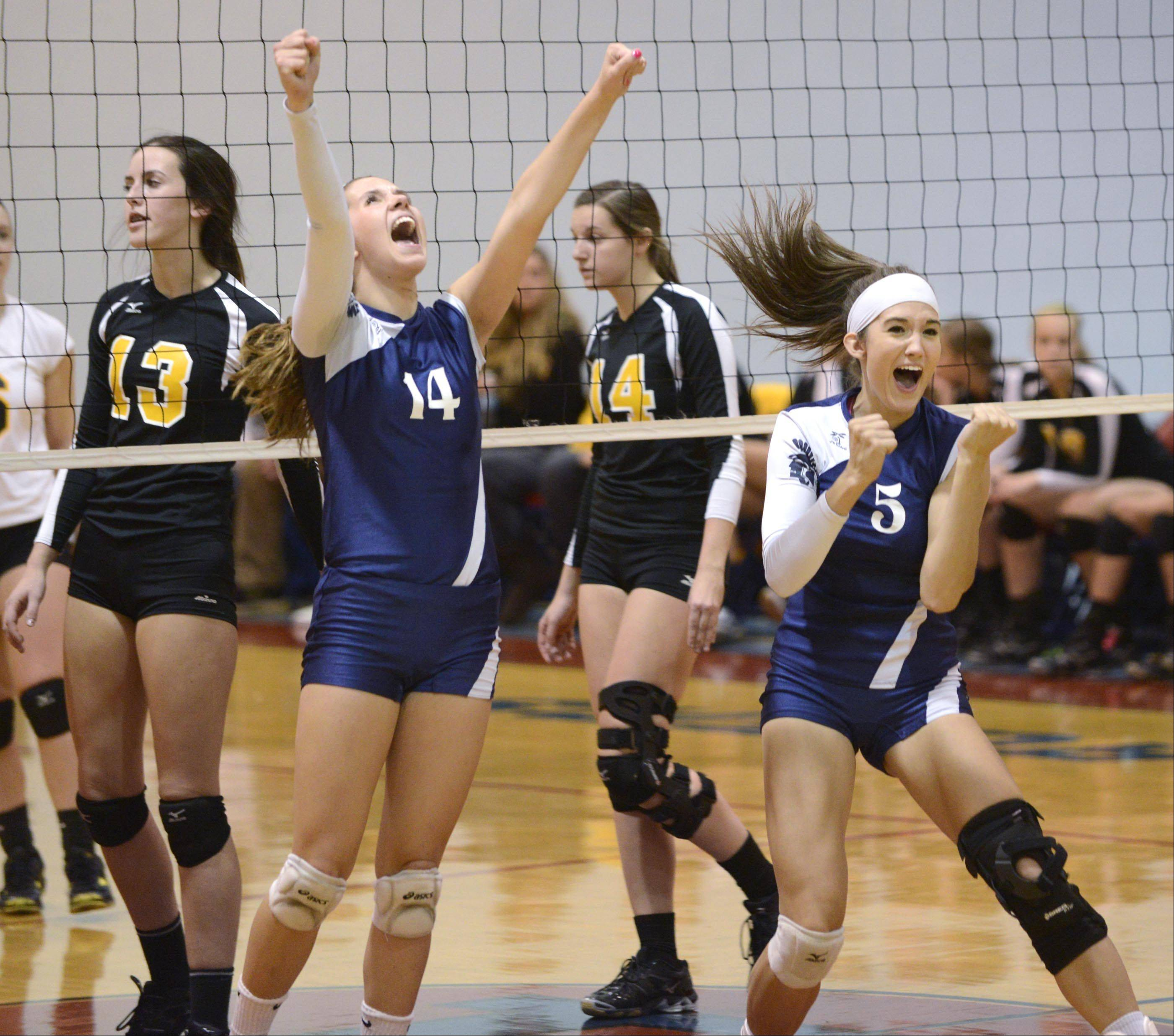Cary-Grove's Sarah Graham and Kayli Trausch, right, exhale in the winning point as Jacobs' Katie Mahoney and Allie Campbell react on the other side of the net Monday in Carpentersville.