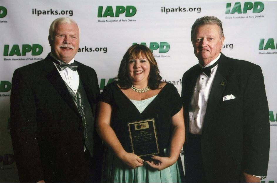 From left, Illinois Association of Park Districts President and CEO Peter Murphy, Schaumburg Park District Cultural Arts Supervisor Beth Waller and IAPD Chairman Don Andersen stand with the Arts in the Park Award.