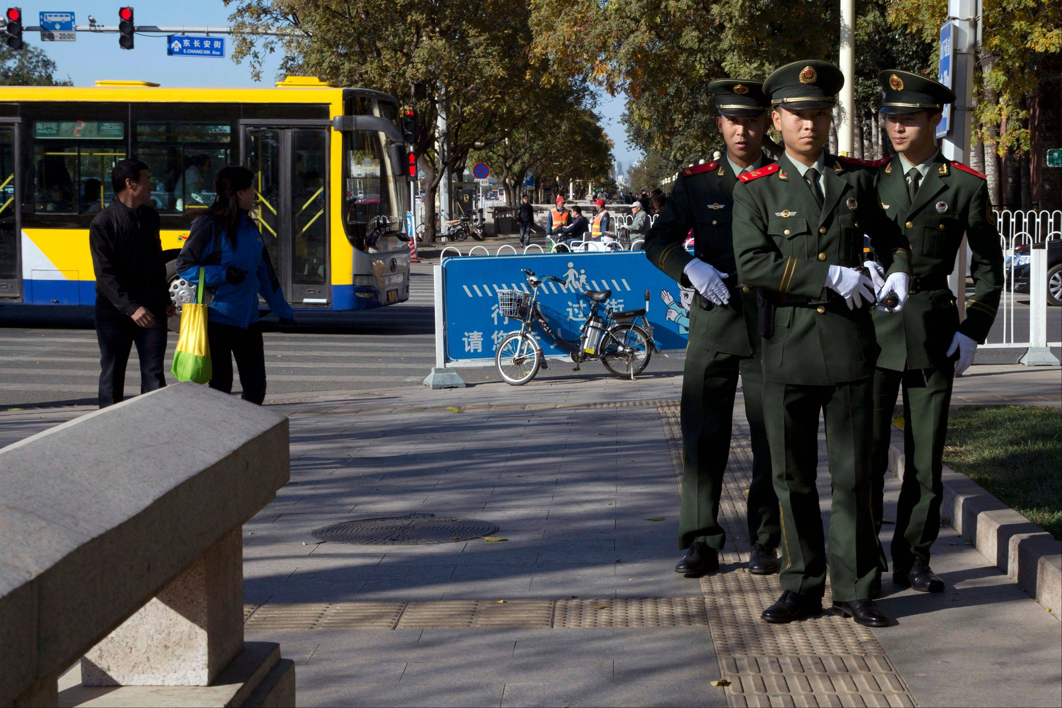 Chinese paramilitary police stand on a sidewalk near the site of Monday�s incident where a car plowed through a crowd before it crashed and burned in Beijing, China, Tuesday.