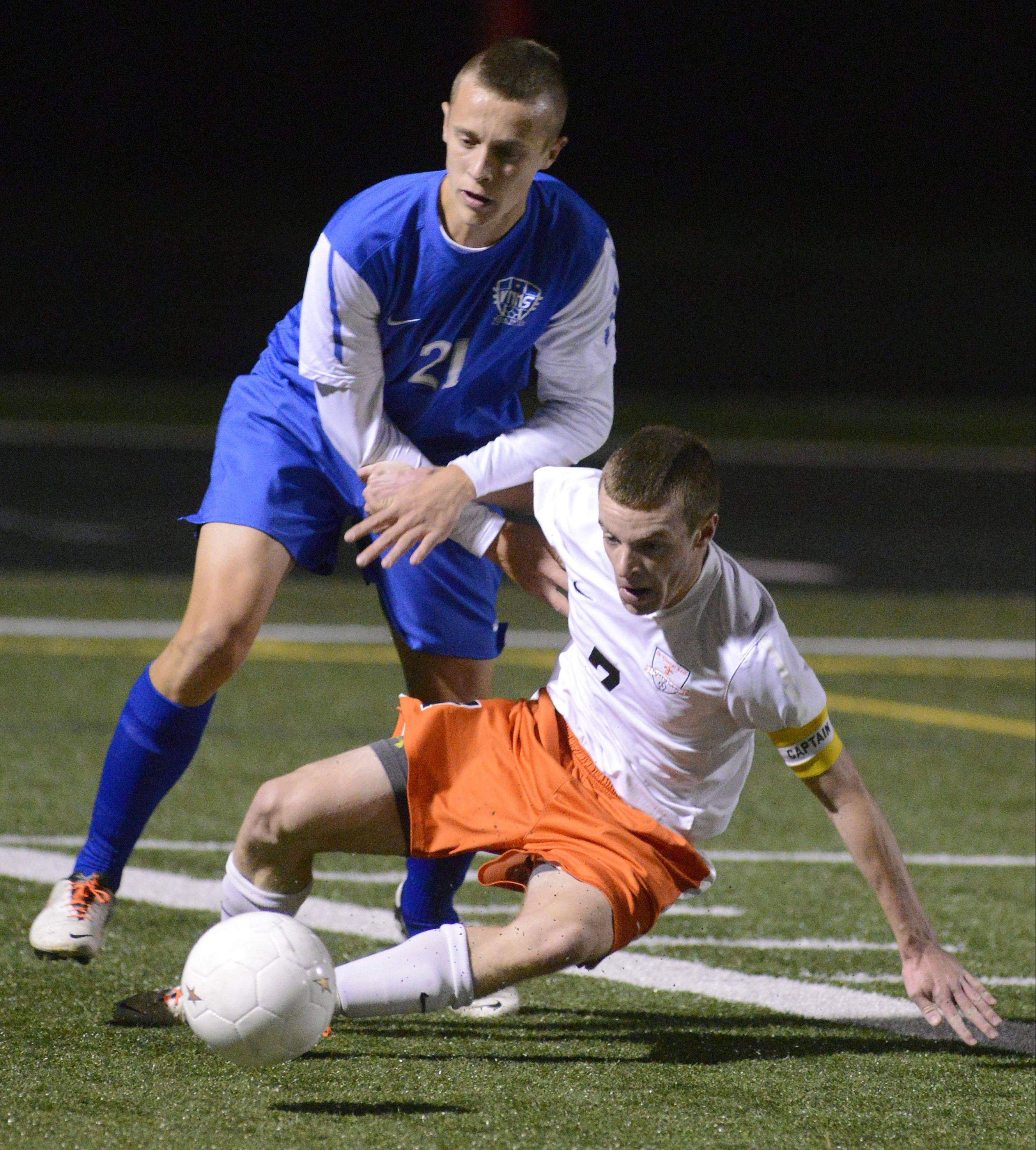 Wheaton North's Zach Oslund and St. Charles East's Jacob Sterling fight for the ball.