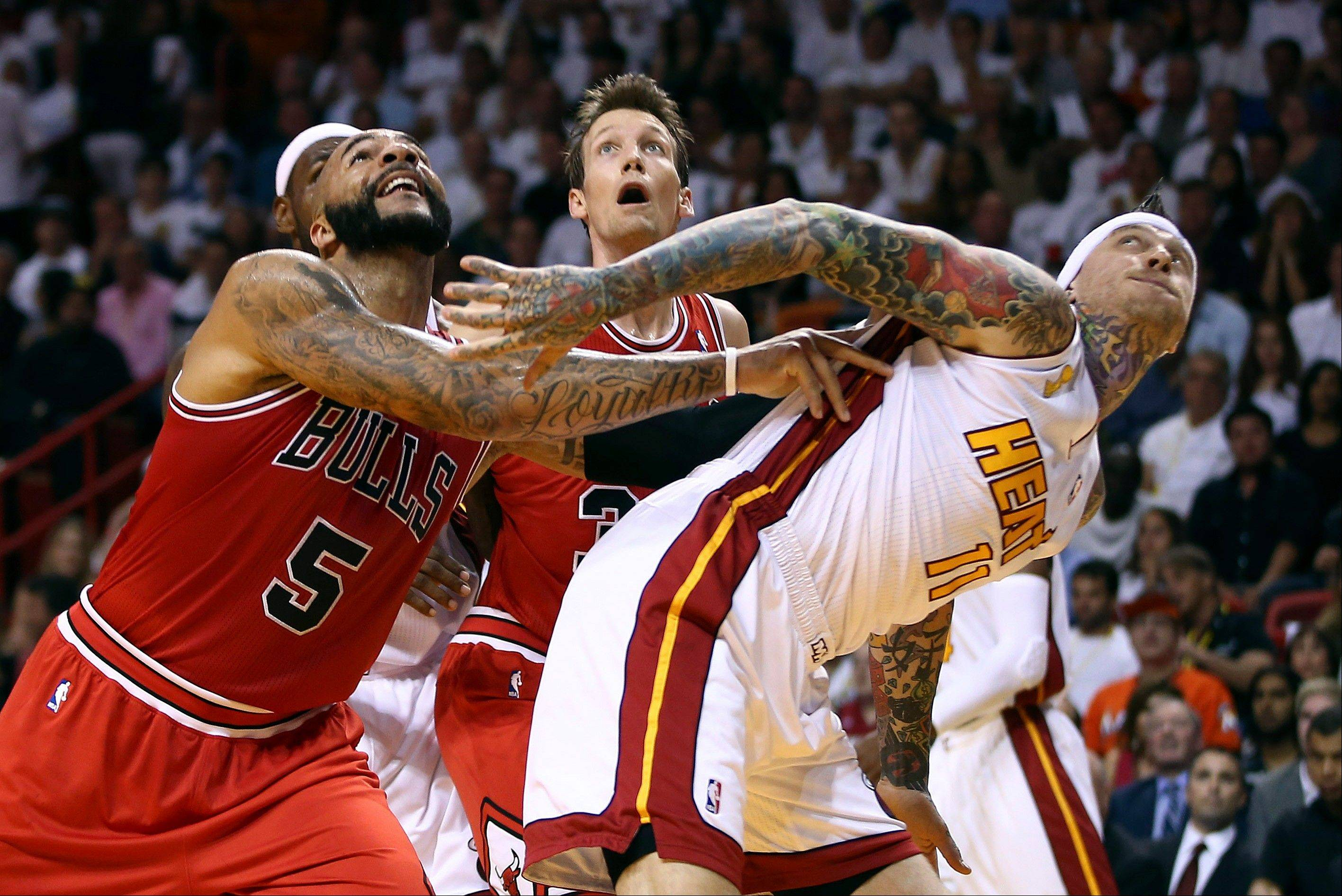 Chicago Bulls Carlos Boozer (5) and Mike Dunleavy battle for a rebound with the Miami Heat's Chris Andersen (11) during the first half of an NBA basketball game in Miami, Tuesday, Oct. 29, 2013.