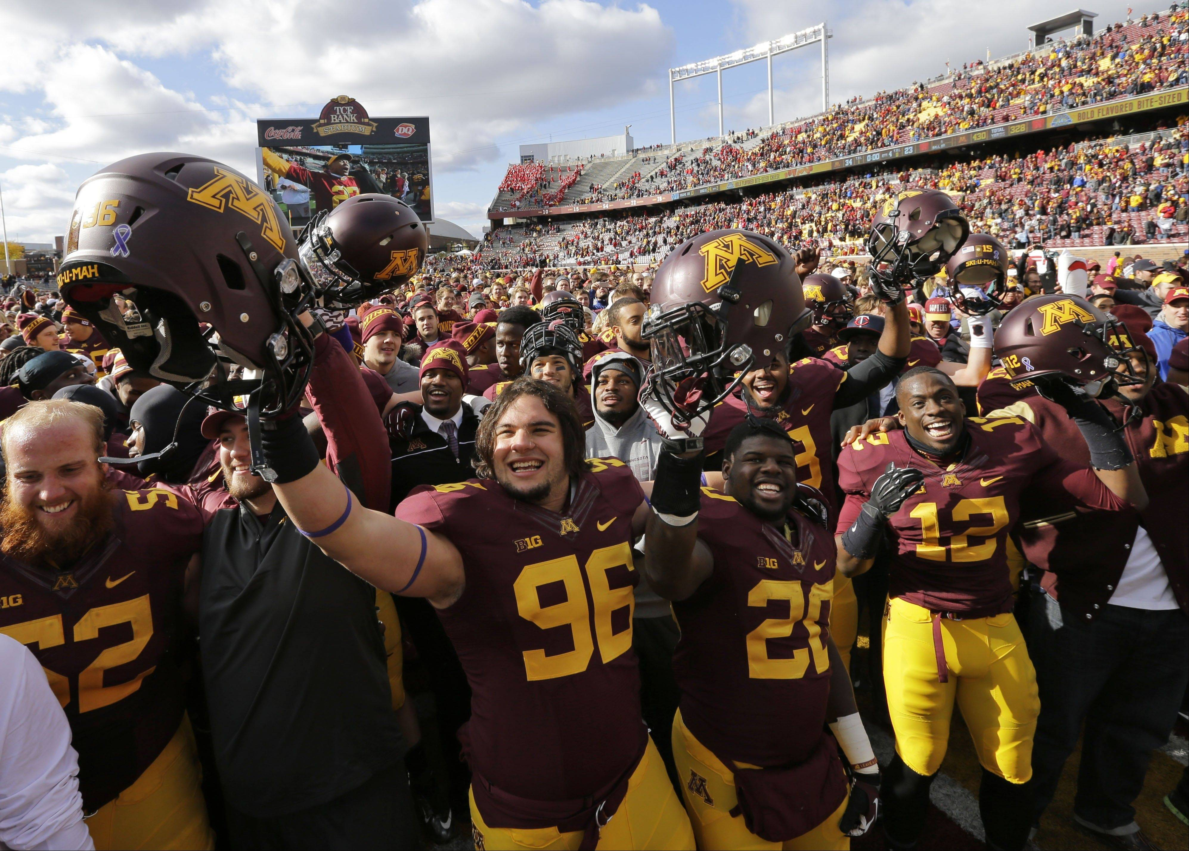 Minnesota defensive lineman Jordan Hinojosa (96), his teammates and fans celebrate after the Gophers beat No. 25 Nebraska 34-23 on Saturday in Minneapolis.