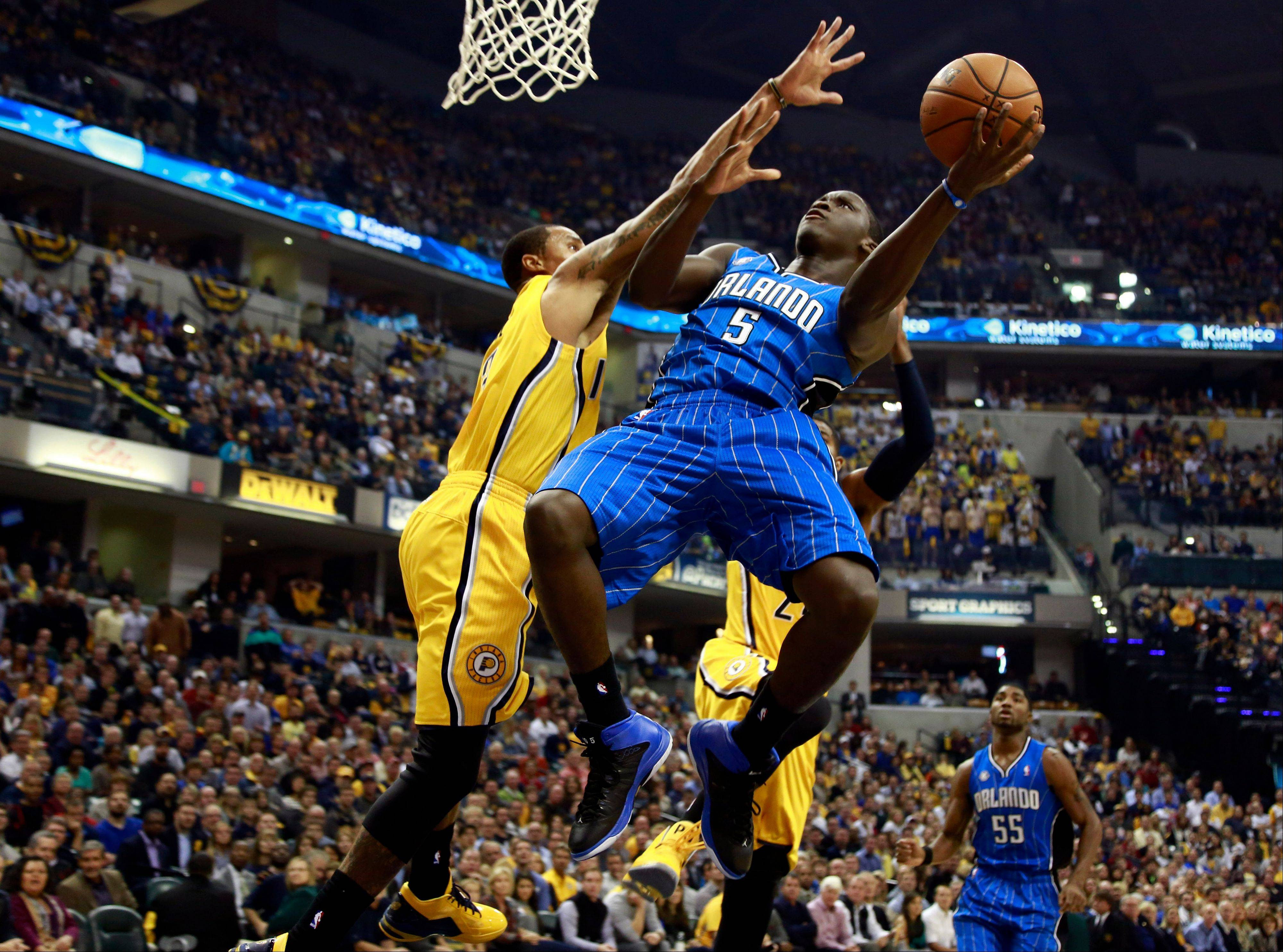 Orlando Magic guard Victor Oladipo (5) puts up a shot while defended by Indiana Pacers guard George Hill in the first half of an NBA basketball game Tuesday in Indianapolis.