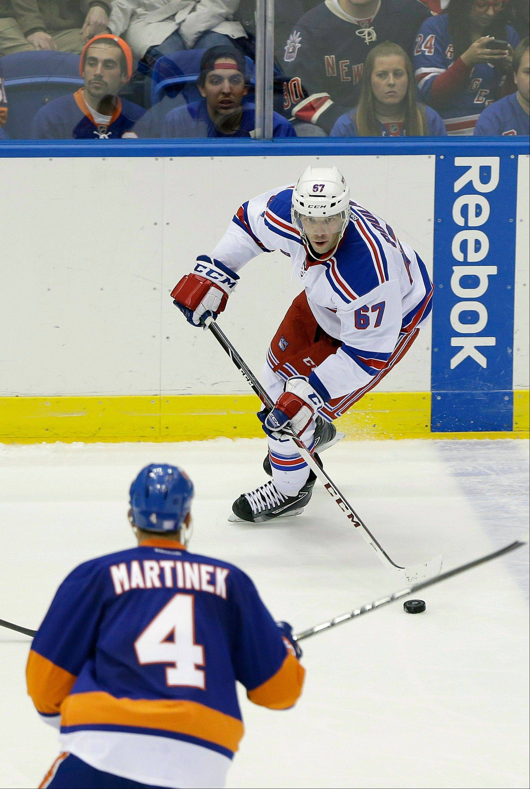 New York Rangers' Benoit Pouliot (67) looks to pass away as New York Islanders' Radek Martinek (4) skates in during the third period of an NHL hockey game Tuesday, in Uniondale, N.Y. The Rangers won the game 3-2.