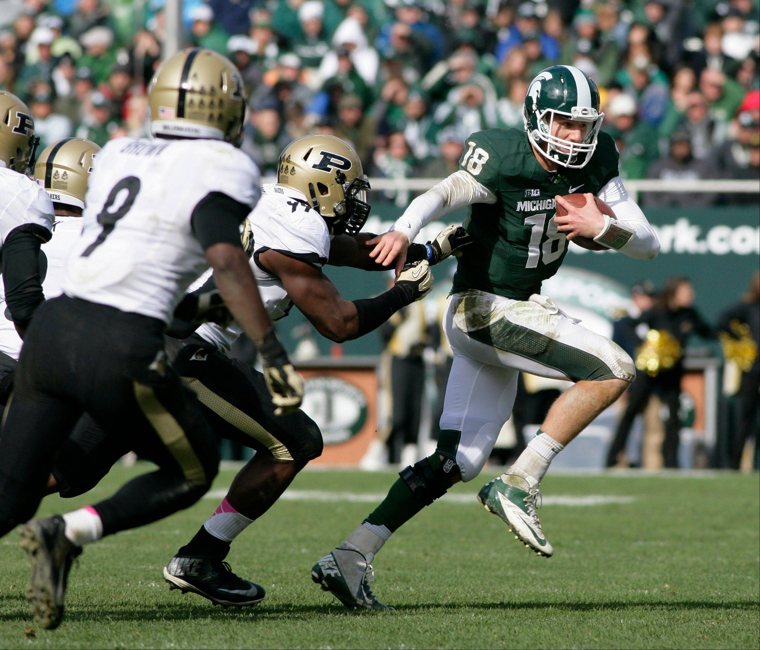 Michigan State quarterback Connor Cook scrambles against Purdue�s Ryan Russell, center, and Anthony Brown during the fourth quarter of the Oct. 19 game in East Lansing, Mich. Heading into the final month of regular season Michigan State is battling for supremacy in the Big Ten�s Legends Division with Michigan and Nebraska.