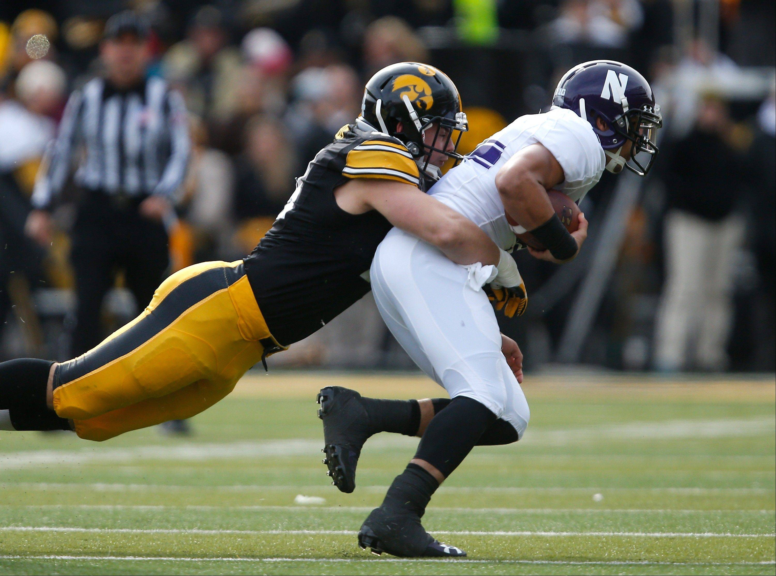 Iowa linebacker James Morris brings down Northwestern quarterback Kain Colter during the first half of Saturday's win in Iowa City.