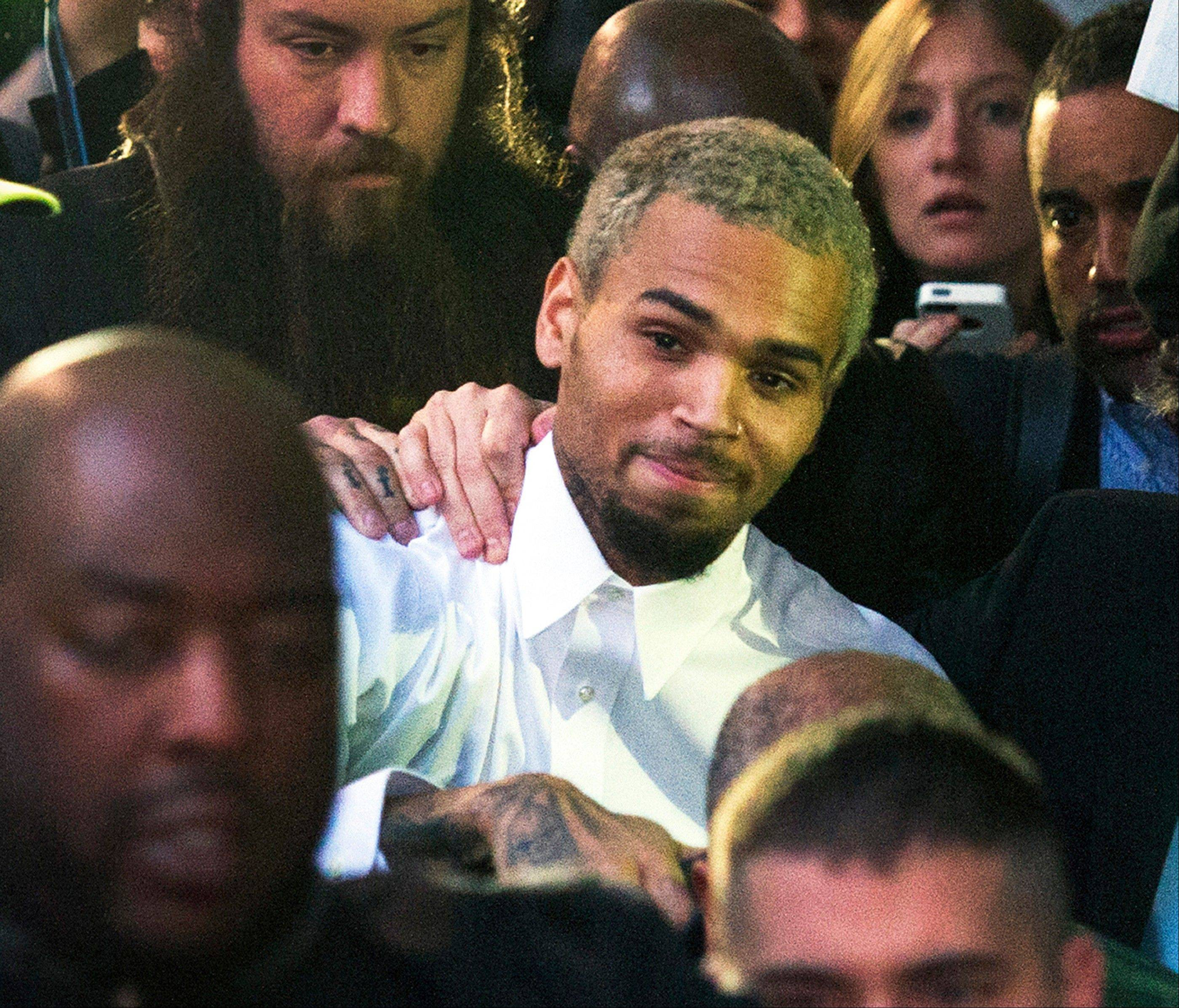 Singer Chris Brown, center, departs the H. Carl Moultriel courthouse Monday in Washington. A charge against the Grammy Award-winning R&B singer has been reduced to a misdemeanor and he was ordered released after his arrest Sunday following an altercation outside a Washington hotel.