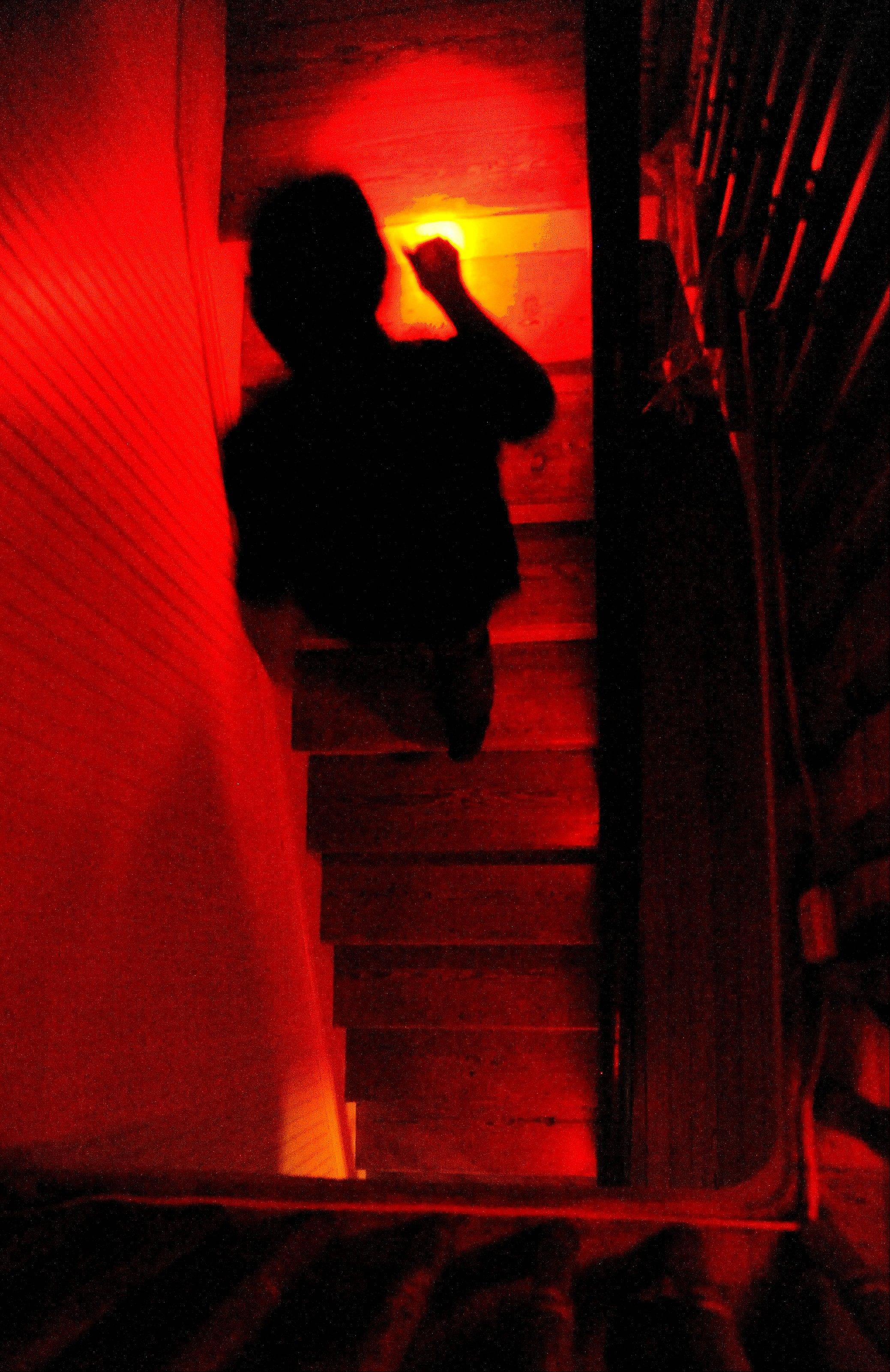Jason Balbuena, paranormal investigator and night tour coordinator at the Pensacola Lighthouse, is silhouetted by his red-gelled flashlight as he walks up a staircase during a ghost tour at the lighthouse in Pensacola, Fla.