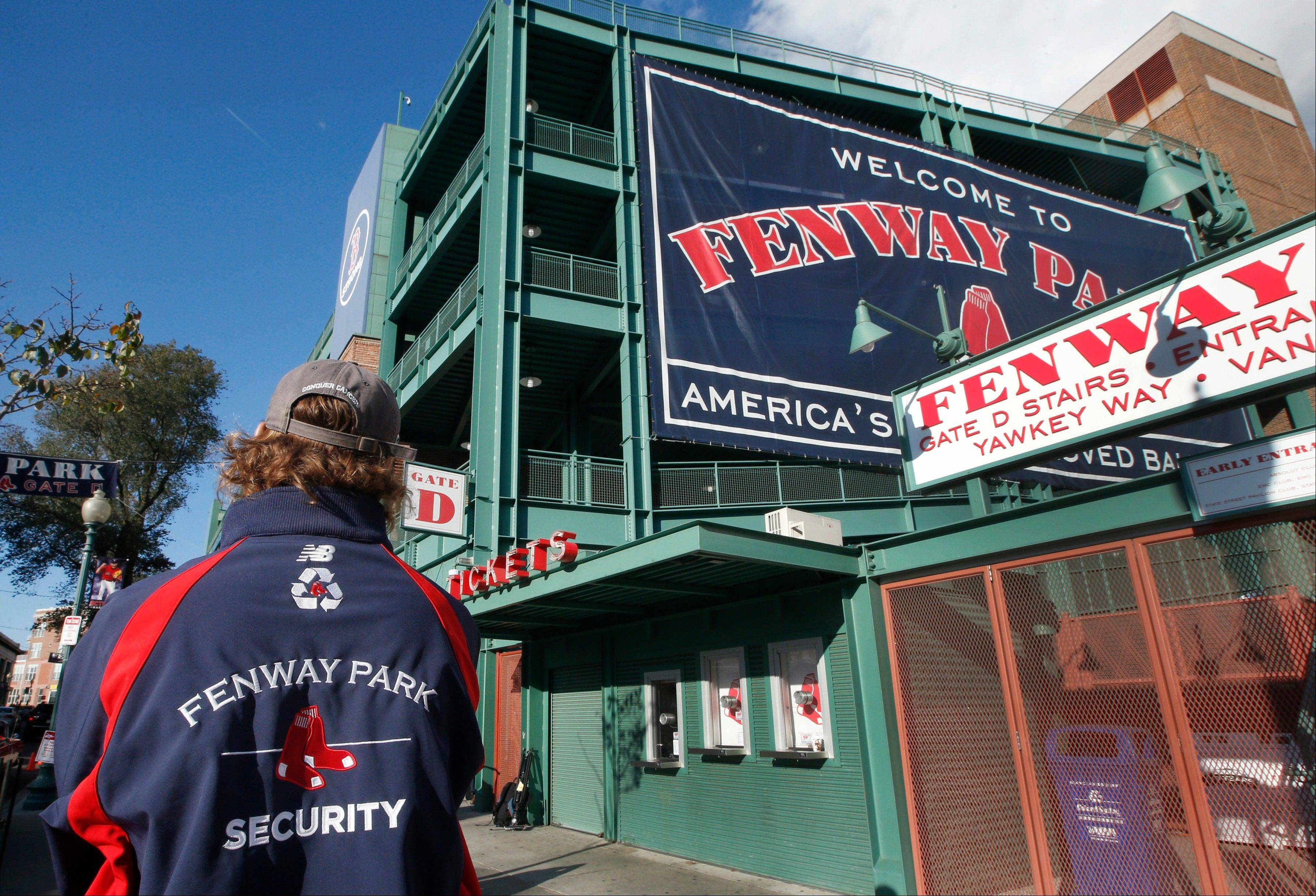 A security guard keeps an eye on things outside Gate D at Fenway Park in Boston on Tuesday. If the Boston Red Sox are able to win the baseball World Series at the stadium, police and city officials want to make sure fans celebrate responsibly.