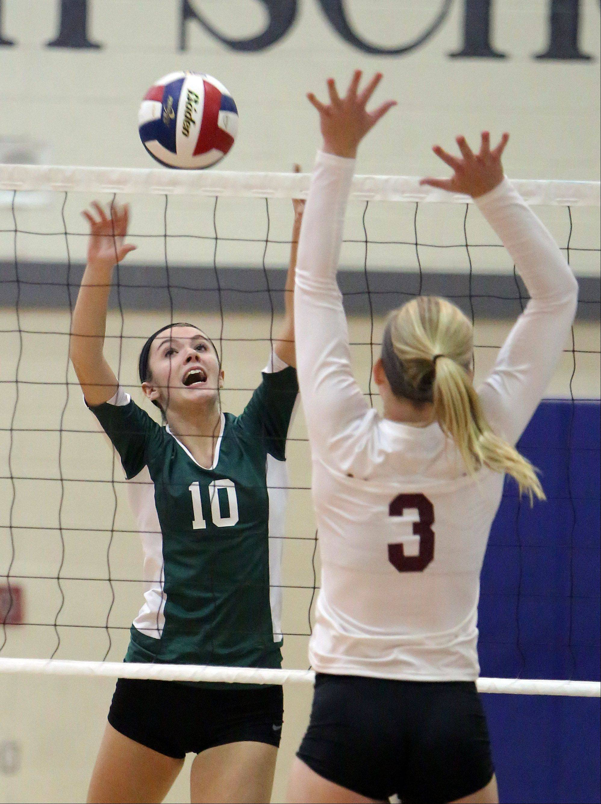 Grayslake Central's Allie Daul, left, and Antioch's Madeline Johnson meet at the net during the girls regional semifinal volleyball game Tuesday at Lakes.