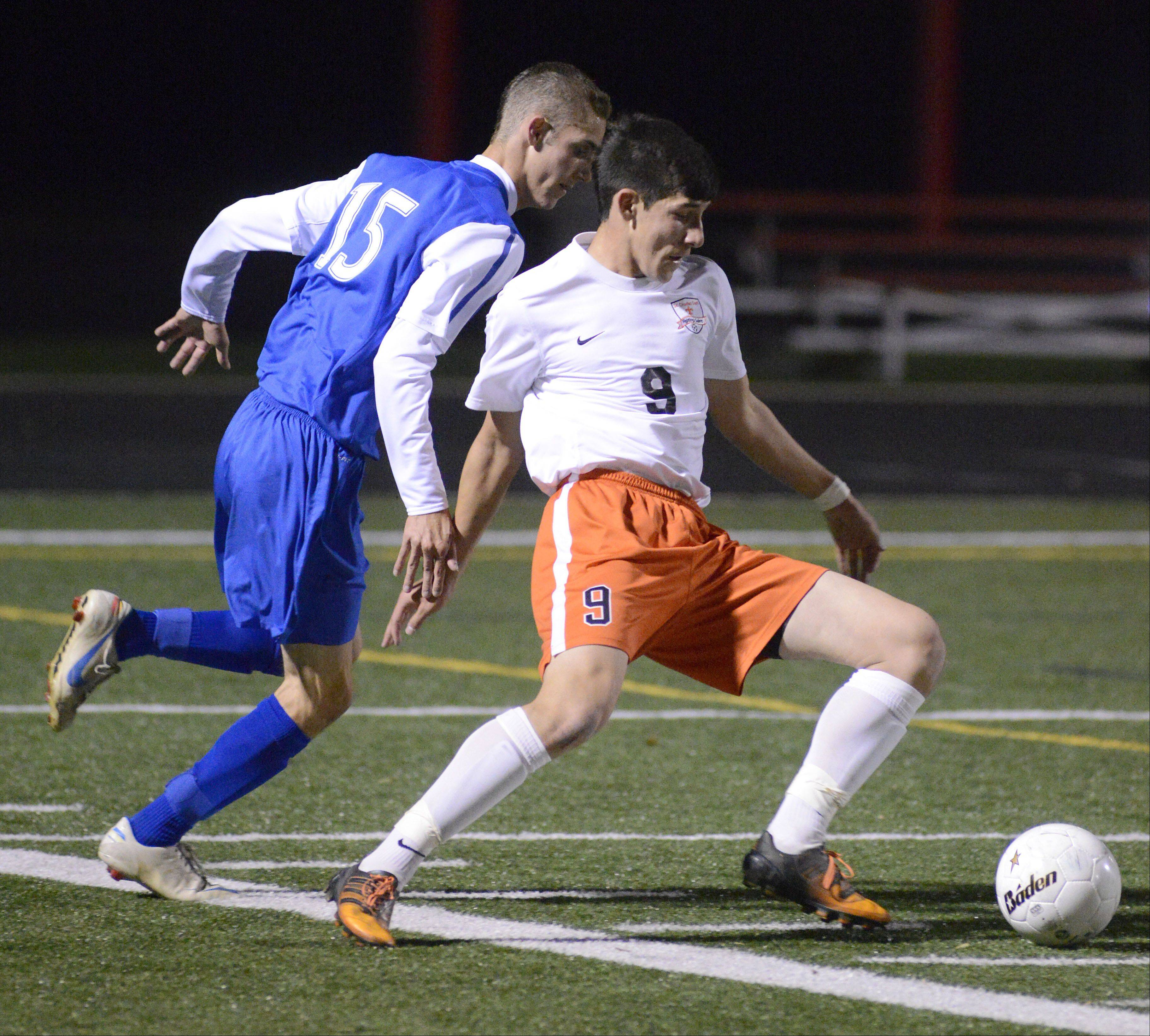 Wheaton North's Jeremy Stapleton and St. Charles East's Taylor Ortiz battle for the ball in the first half of the Schaumburg sectional semifinals on Tuesday, October 29.