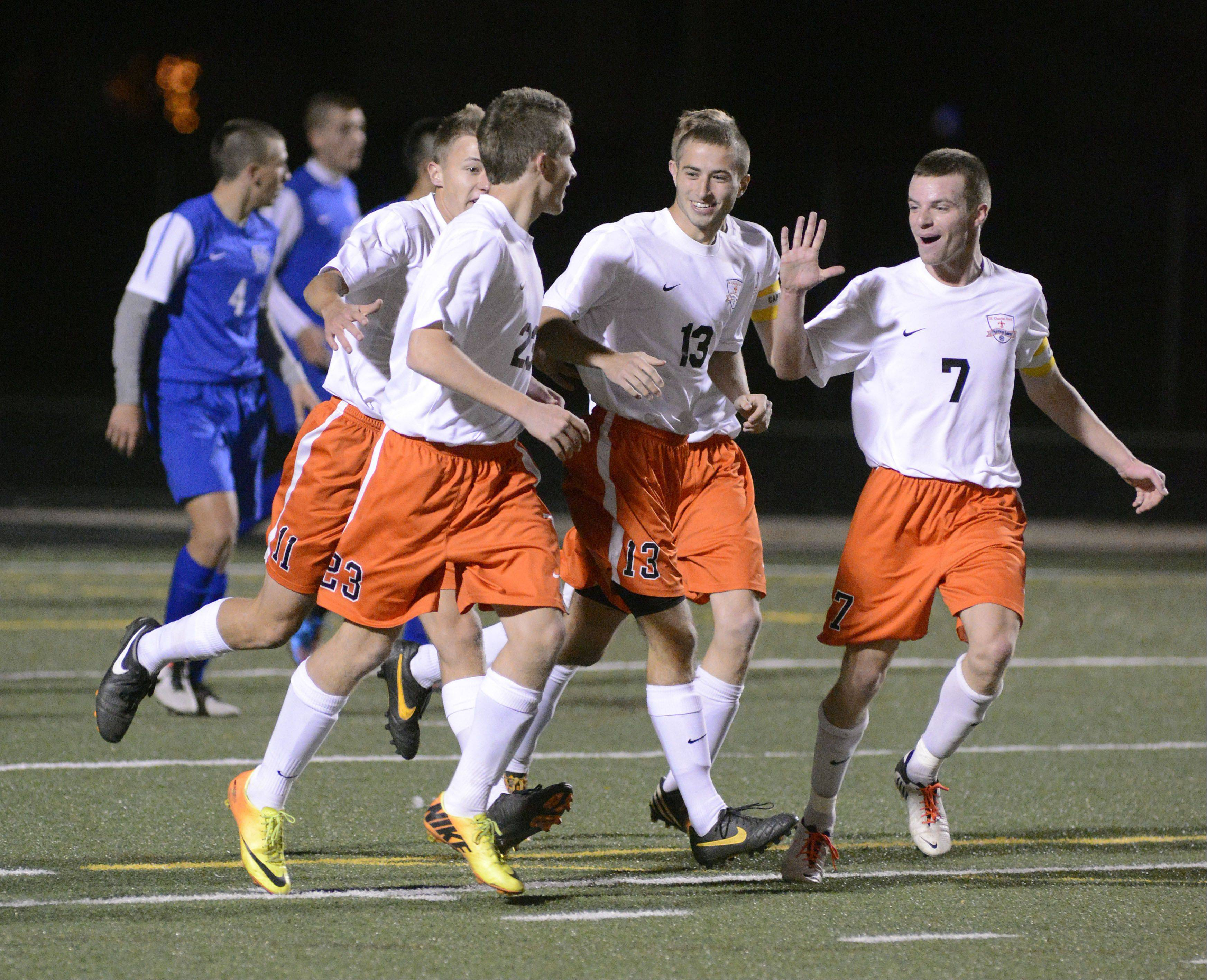 St. Charles East's Tyler Robbins (23) is congratulated by teammates Jeff Chitwood (13) and Jacob Sterling (7) after scoring a goal over Wheaton North in the Schaumburg sectional semifinals on Tuesday, October 29.