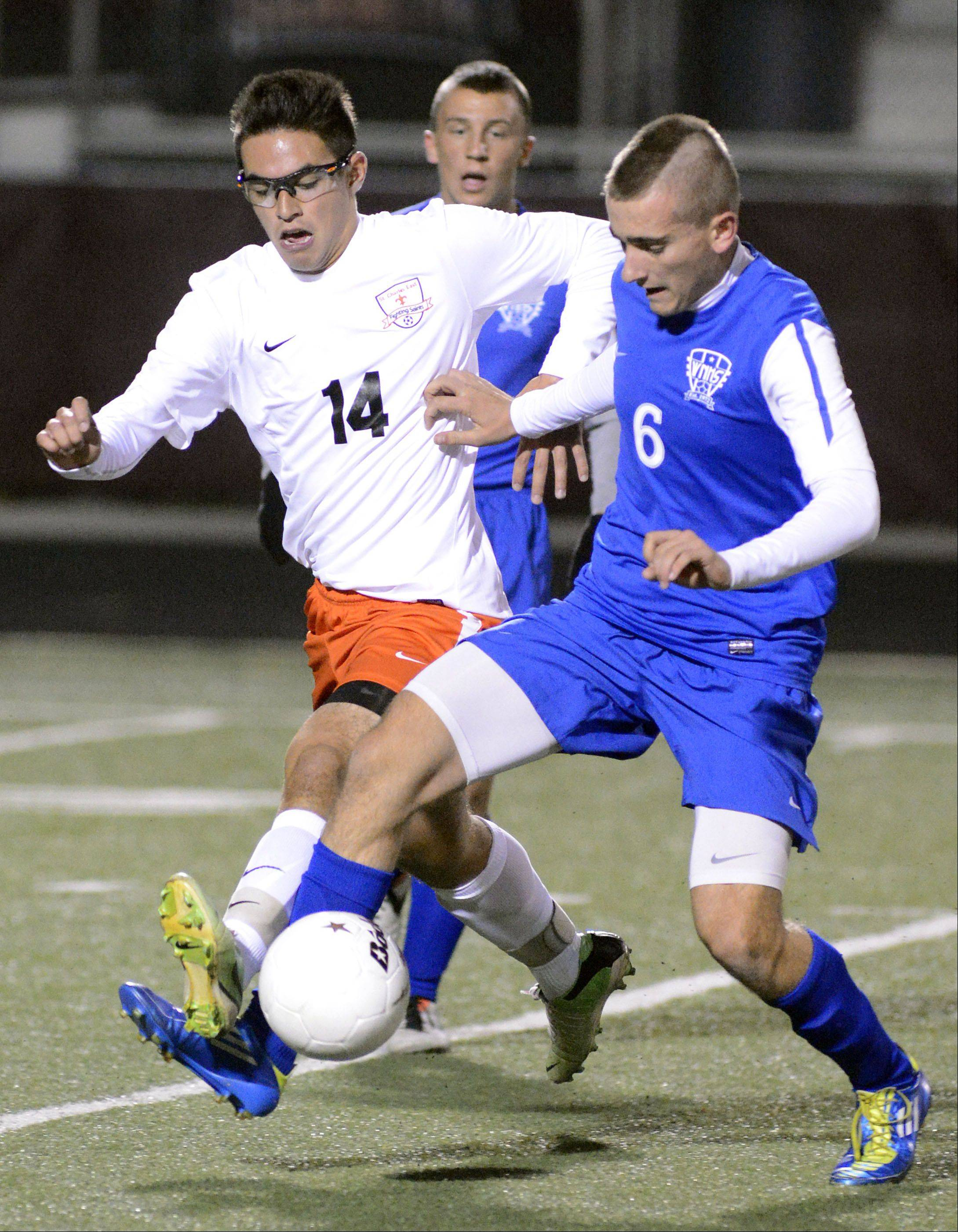 St. Charles East's Zach Manibog and Wheaton North's Jason Szumski fight for the ball in the first half of the Schaumburg sectional semifinals on Tuesday, October 29.