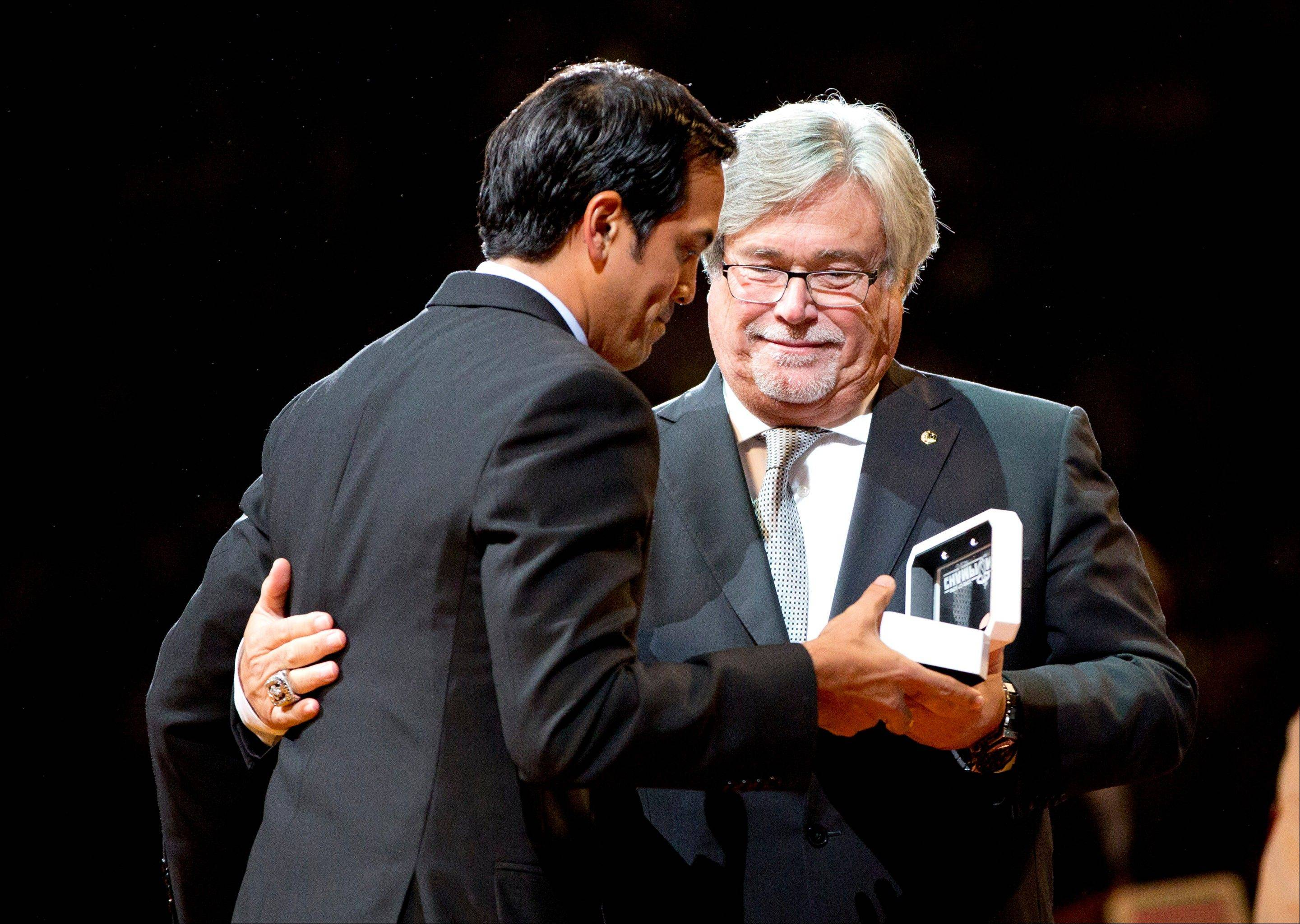 Miami Heat coach Erik Spoelstra, left, gets his championship ring from team owner Micky Arison, right, during a ceremony before their season-opening NBA basketball game against the Chicago Bulls, Tuesday, Oct. 29, 2013, in Miami.