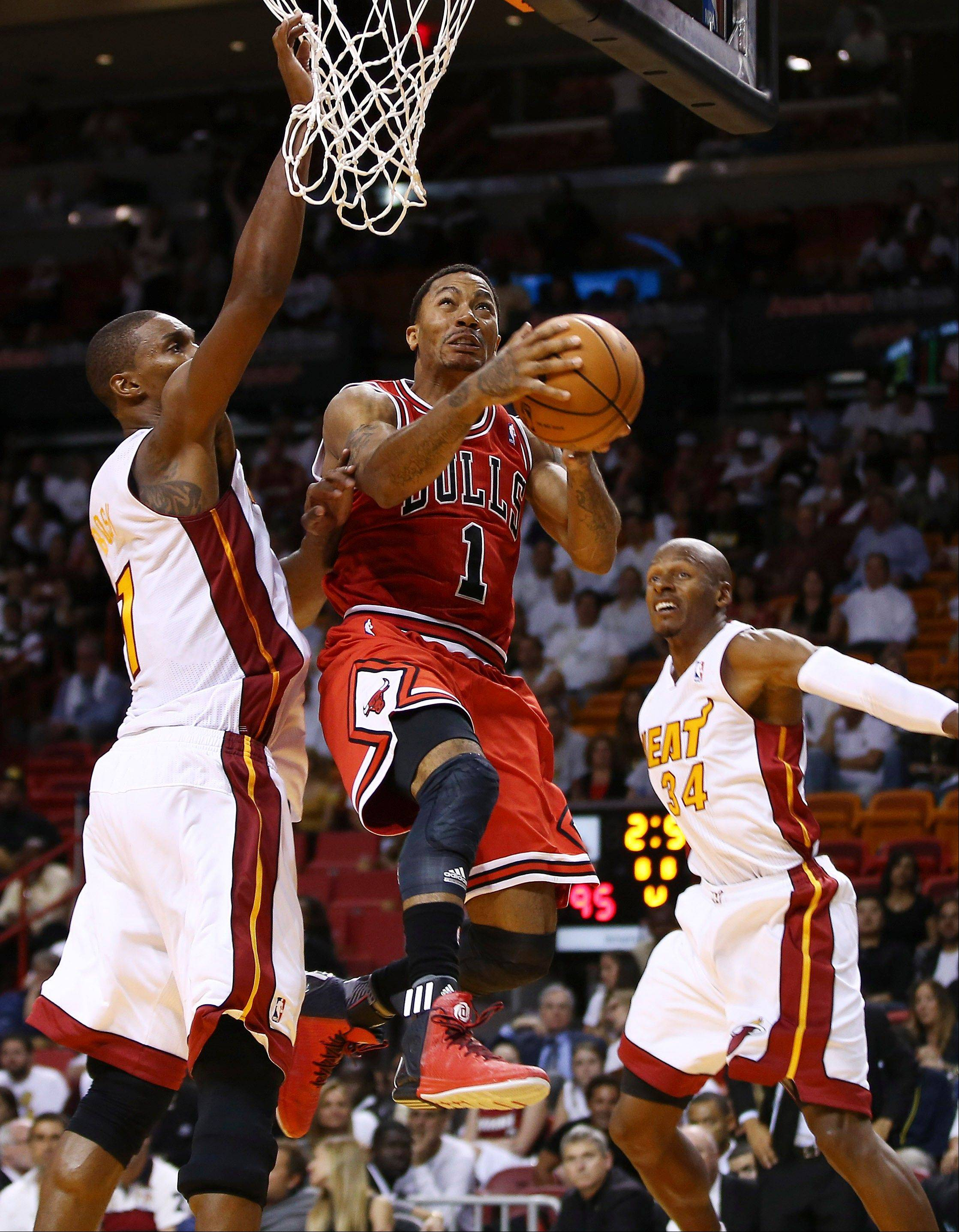 Chicago Bulls' Derrick Rose (1) goes to the basket between Miami Heat's Chris Bosh (1) and Ray Allen (34) during the second half of an NBA basketball game in Miami, Tuesday, Oct. 29, 2013. Rose missed the shot. The Heat won 107-95.
