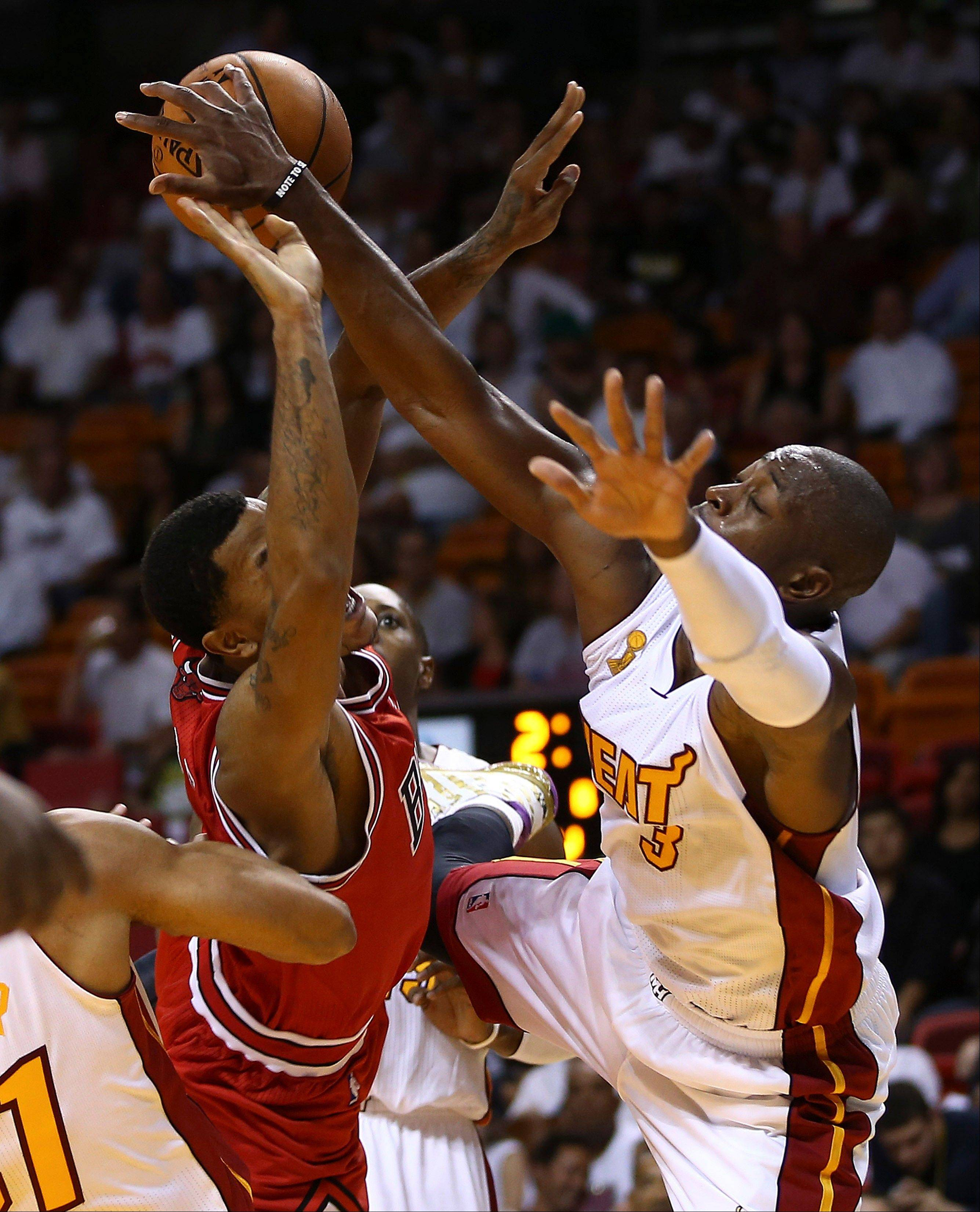 Miami Heat's Dwyane Wade (3) blocks a shot by Chicago Bulls' Derrick Rose during the second half of an NBA basketball game in Miami, Tuesday, Oct. 29, 2013. The Heat won 107-95.