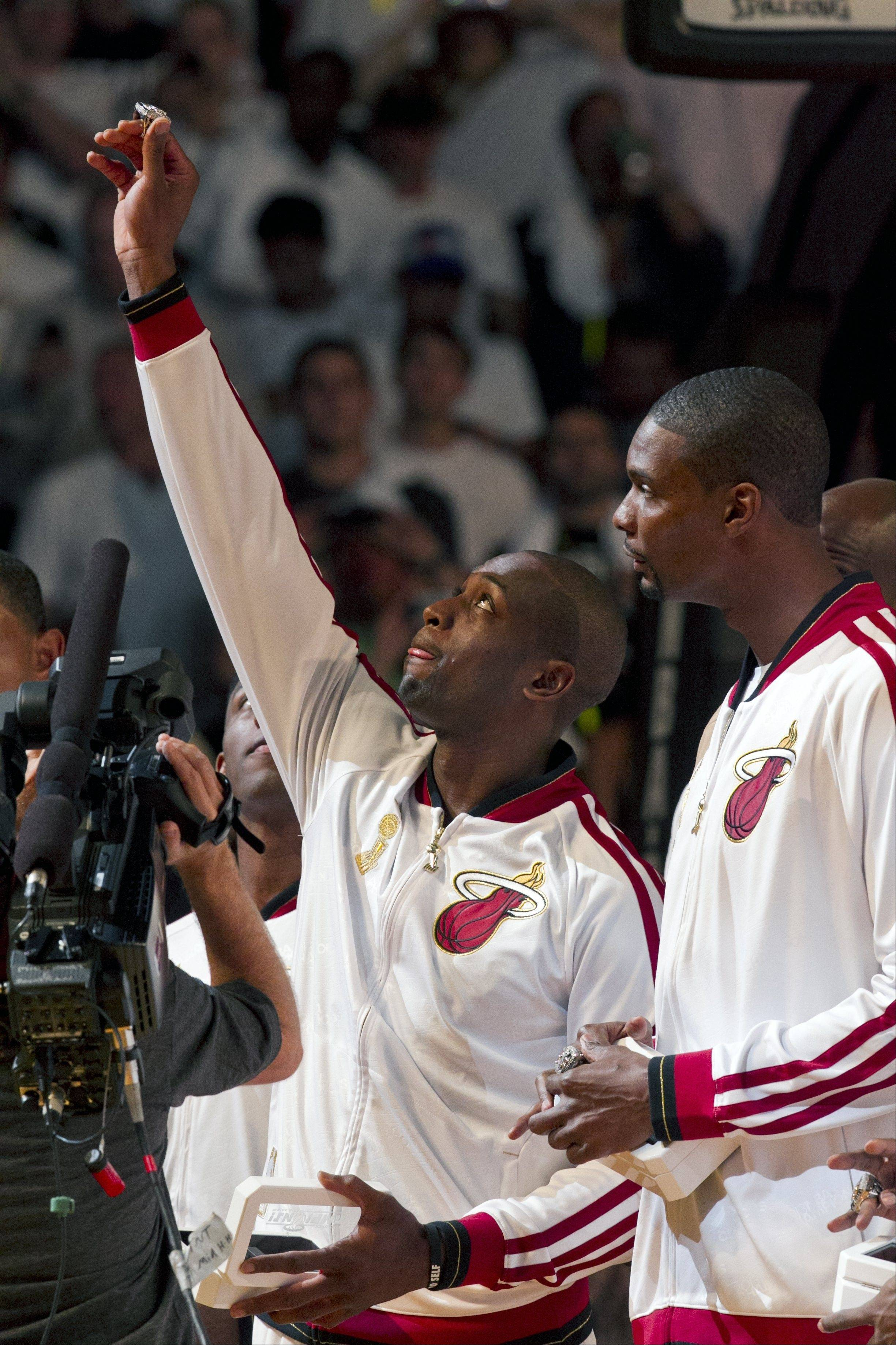 Miami Heat's Dwyane Wade, left, holds up his championship ring as Chris Bosh looks on during a ceremony before their season-opening NBA basketball game against the Chicago Bulls, Tuesday, Oct. 29, 2013, in Miami.