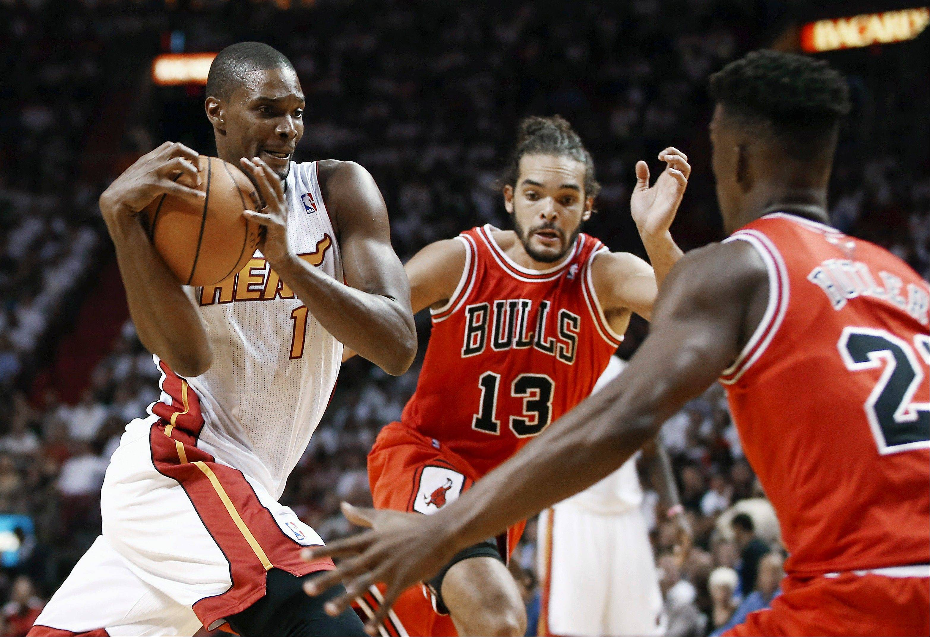 Miami Heat's Chris Bosh (1) tries to drive between Chicago Bulls' Joakim Noah (13) and Jimmy Butler (22) during the first half of an NBA basketball game in Miami, Tuesday, Oct. 29, 2013.