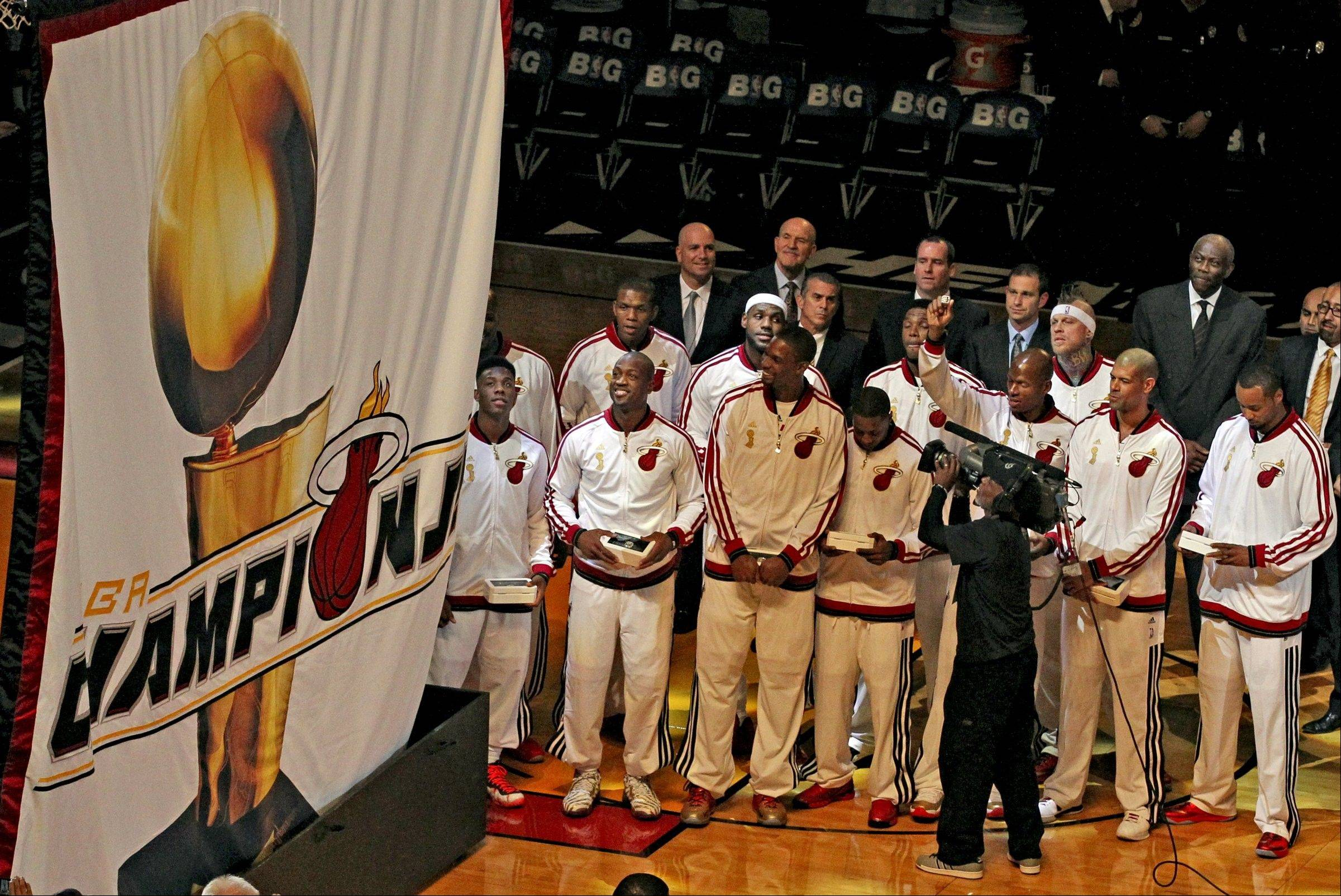 Miami Heat players and coaches watch as the 2013 NBA championship banner is raised before the Heat's season-opener basketball game against the Chicago Bulls on Tuesday, Oct. 29, 2013, in Miami.