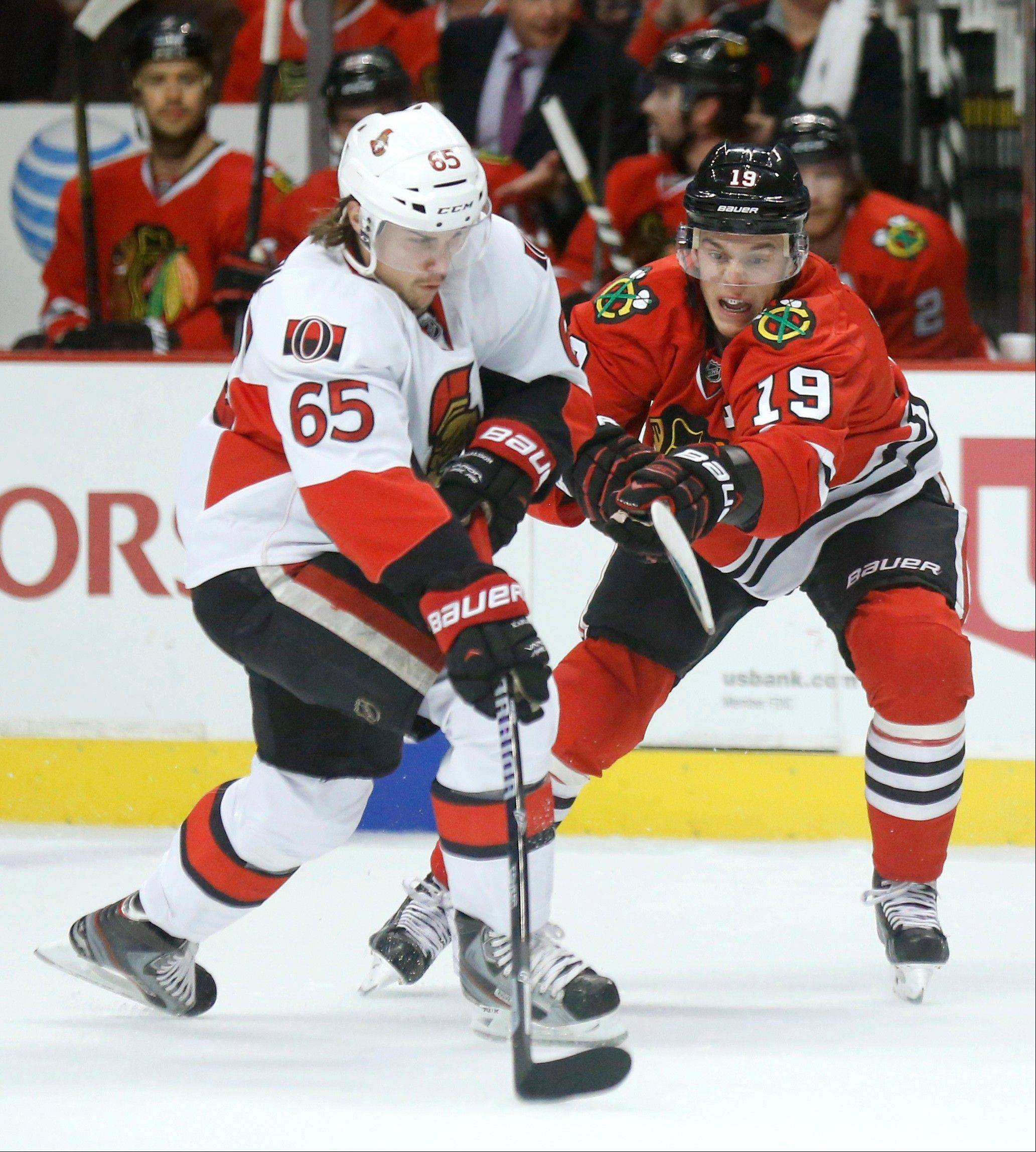 Ottawa Senators defenseman Erik Karlsson (65) passes the puck past Chicago Blackhawks center Jonathan Toews (19) during the first period of an NHL hockey game Tuesday in Chicago. Toews would later get his revenge with three goals during the game and a win over the Senators.
