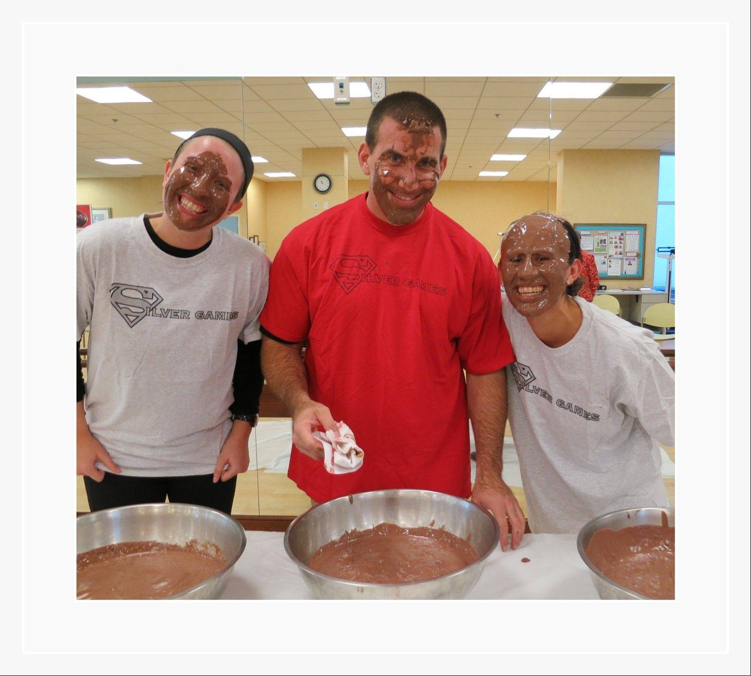 After residents at Friendship Village successfully completed a walking challenge, fitness physiologists Jenna Belt, Jessica Enriquez and AJ Alfrey dunked their heads into bowls of chocolate pudding to fulfill a promise made to the seniors.