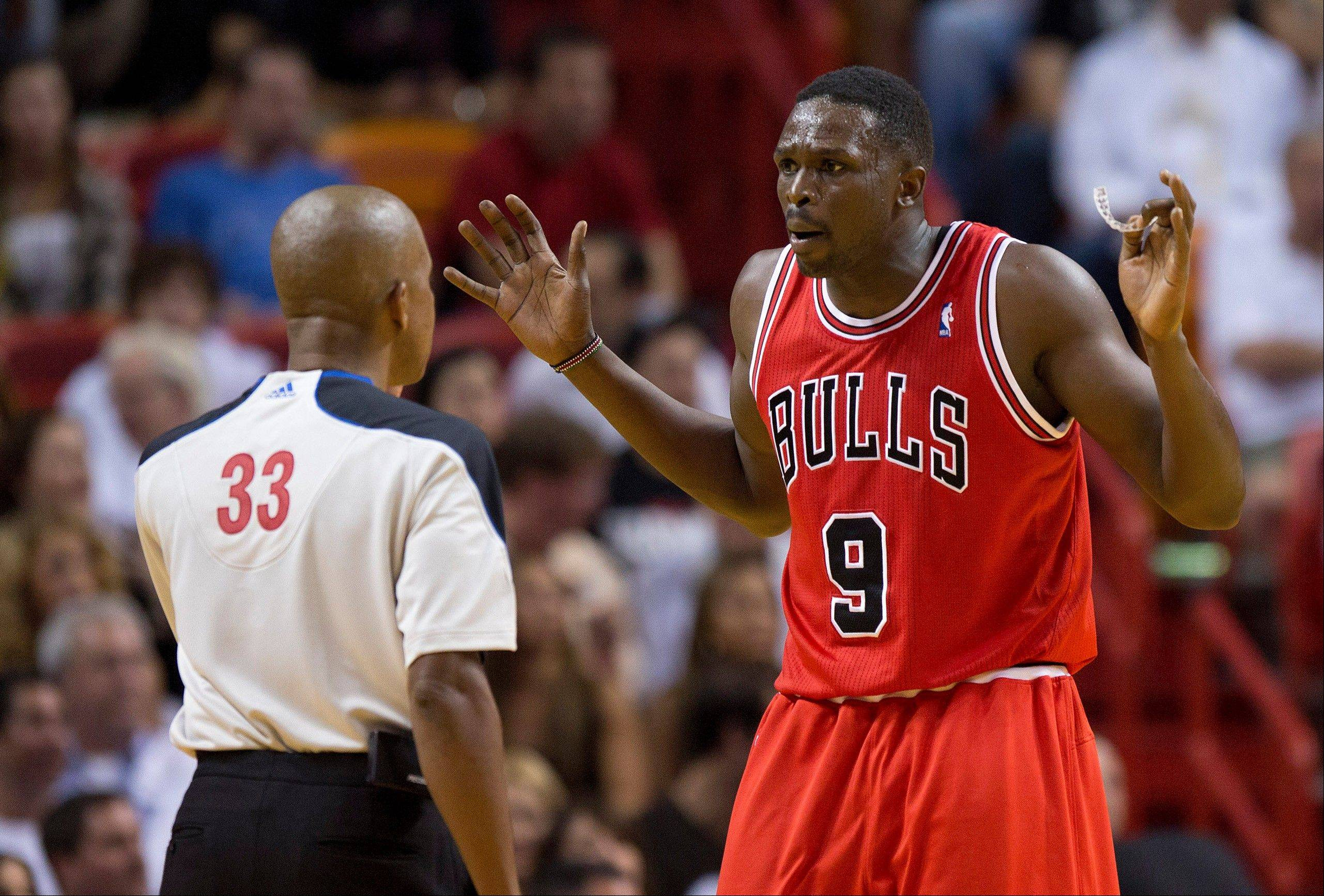 The Bulls� Luol Deng protests a foul call to official Sean Corbin during Tuesday�s season-opening loss at Miami. Deng was on the bench with 3 fouls during a 17-0 Heat run in the second quarter.