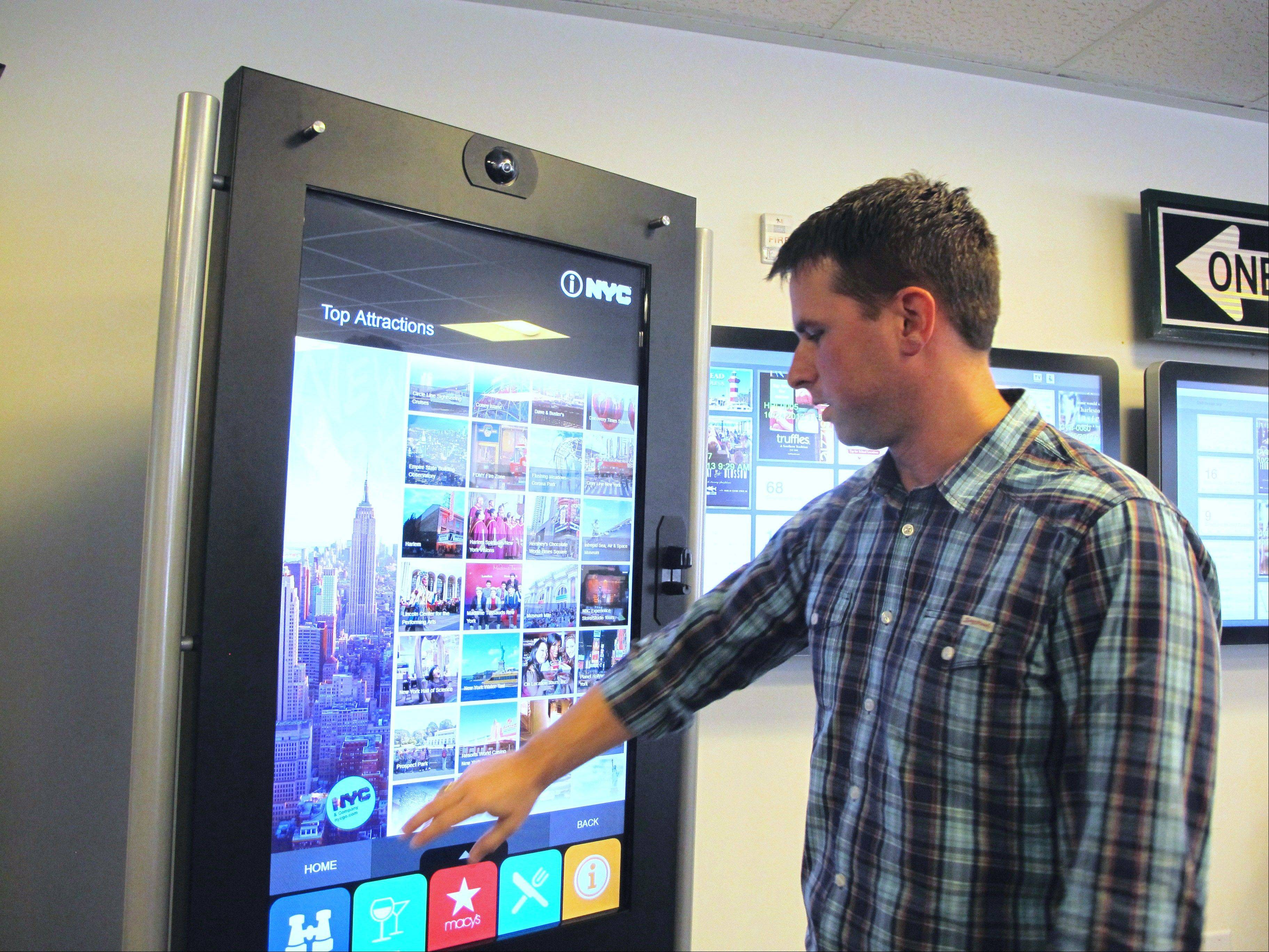 Chad Priest, the chief operating officer for City Corridor, demonstrates a touch-screen interactive visitor kiosk in the company's offices in North Charleston, S.C. The interactive kiosk allows visitors to click and print out everything from maps to menus and buy tickets for attractions.