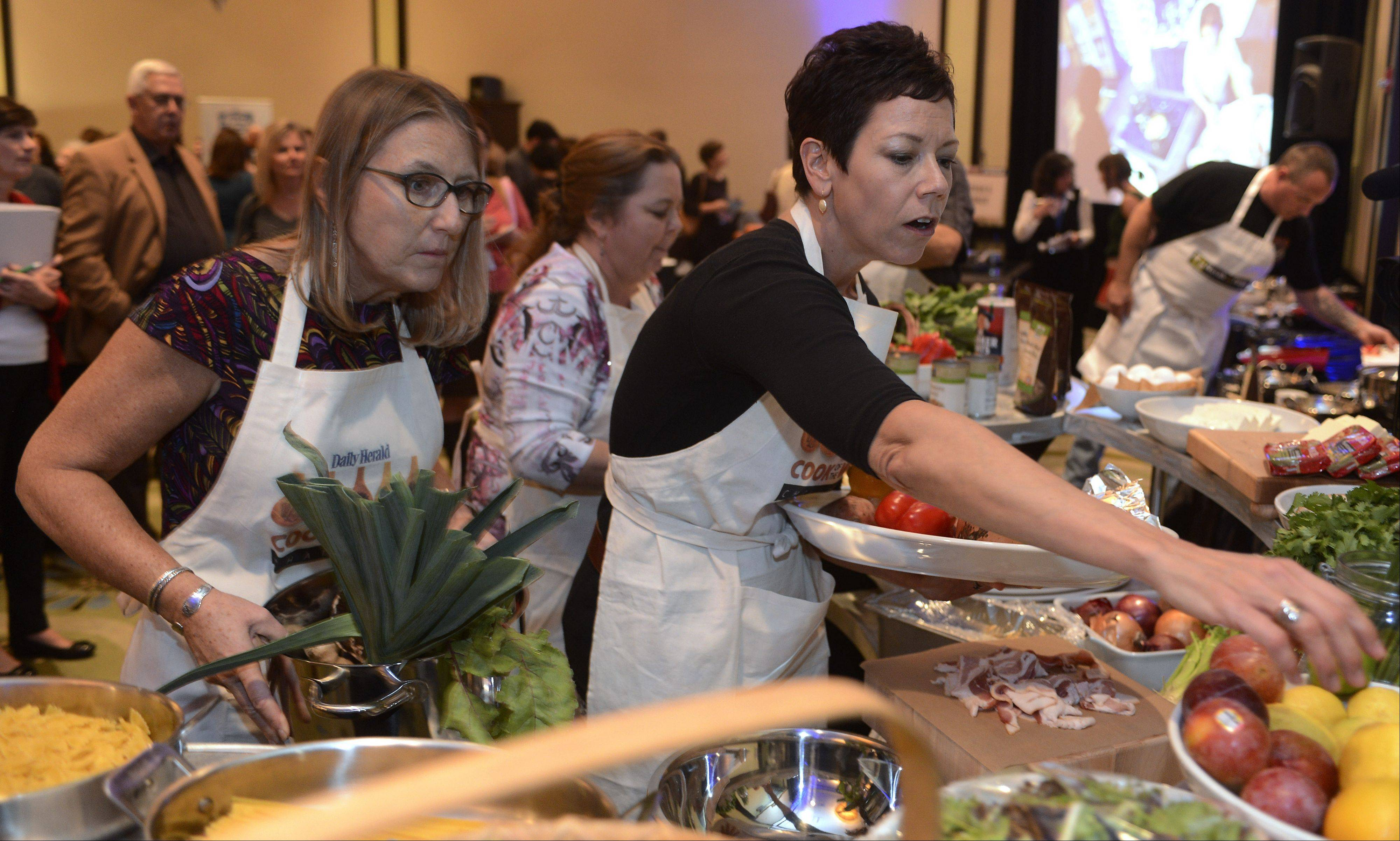 Contestants Christine Murphy, left, and Lori Motyka select items from the pantry during the Daily Herald Cook of the Week Cookoff finals, held at the Hyatt Regency Schaumburg Wednesday.