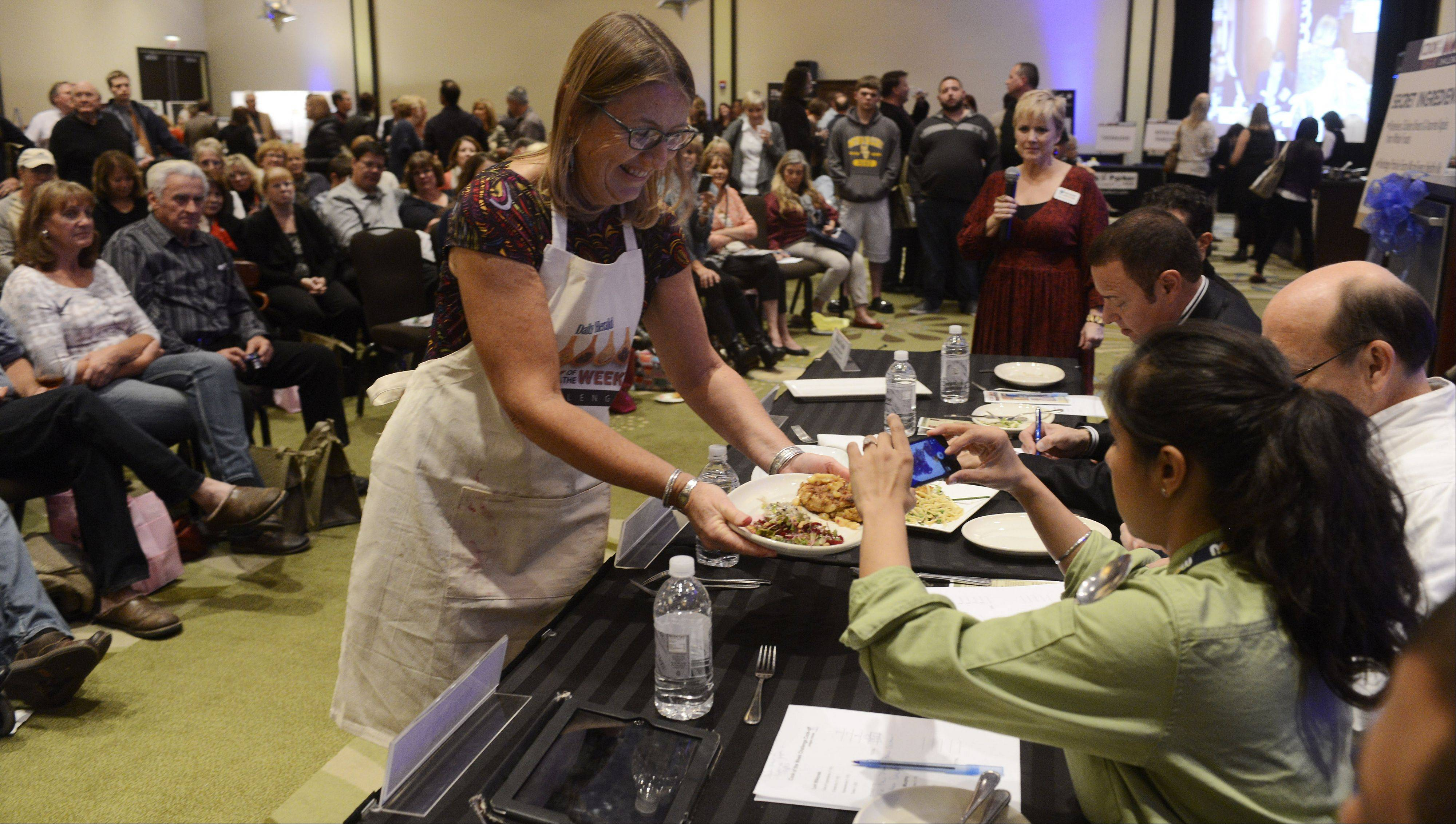 Christine Murphy of Palatine shows judges her dish during the Daily Herald Cook of the Week Cookoff finals, held at the Hyatt Regency Schaumburg Wednesday.