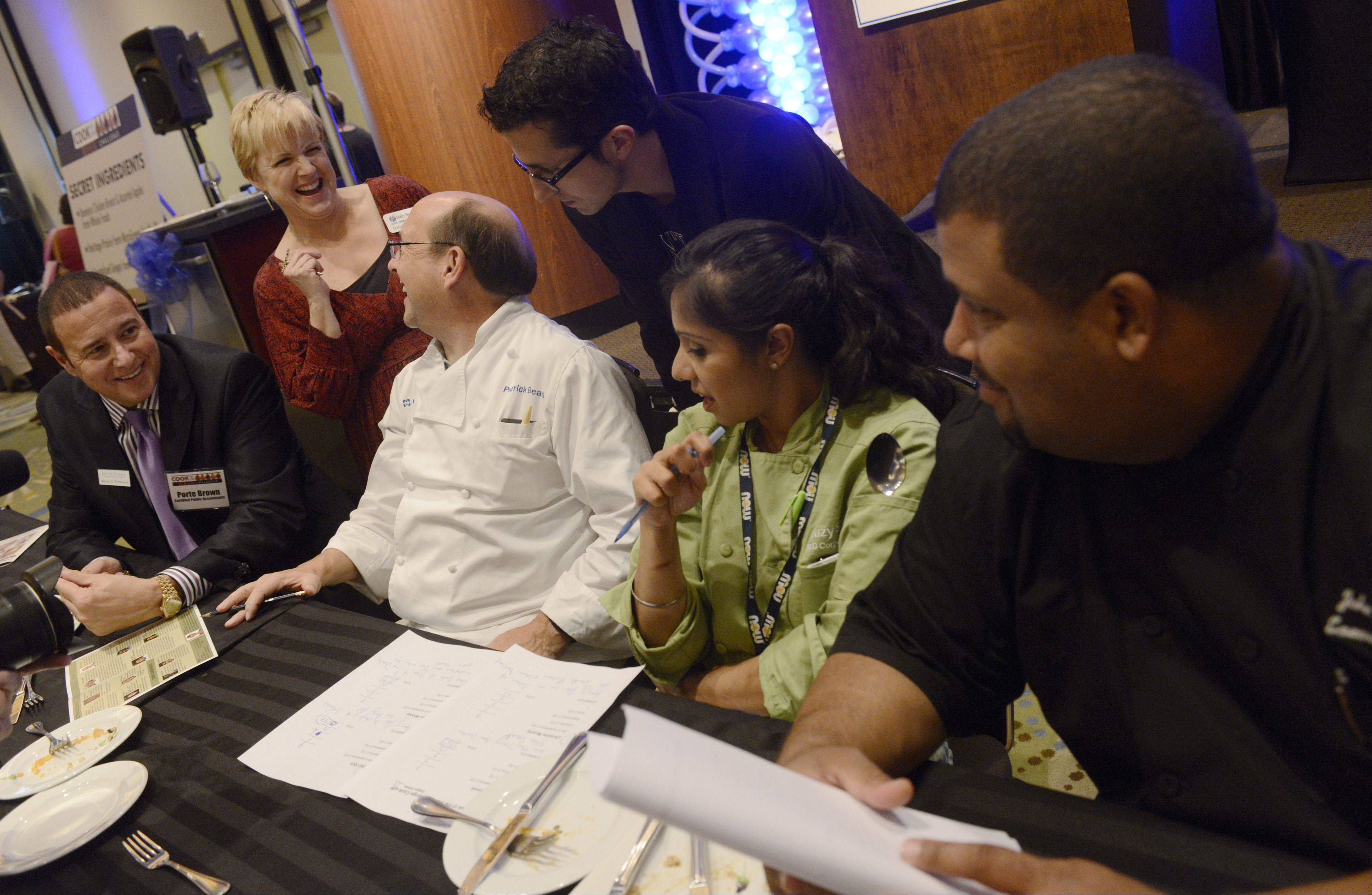 Daily Herald Food Editor Deb Pankey, top left, confers with the judges during the Daily Herald Cook of the Week Cookoff finals, held at the Hyatt Regency Schaumburg Wednesday.