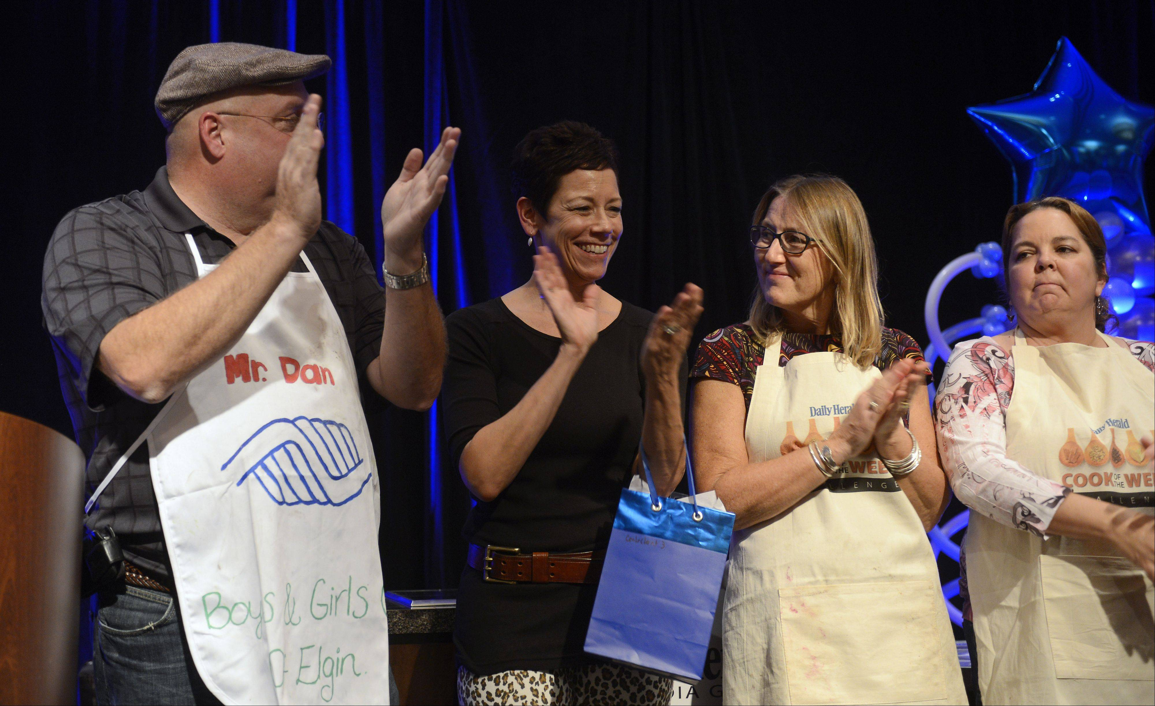 Lori Motyka of West Chicago, second from left, claps her hands after being announced the runner-up during the Daily Herald Cook of the Week Cookoff finals, held at the Hyatt Regency Schaumburg Wednesday. With her on stage are fellow contestants Dan Rich, Christine Murphy and Lori Wiktorek.