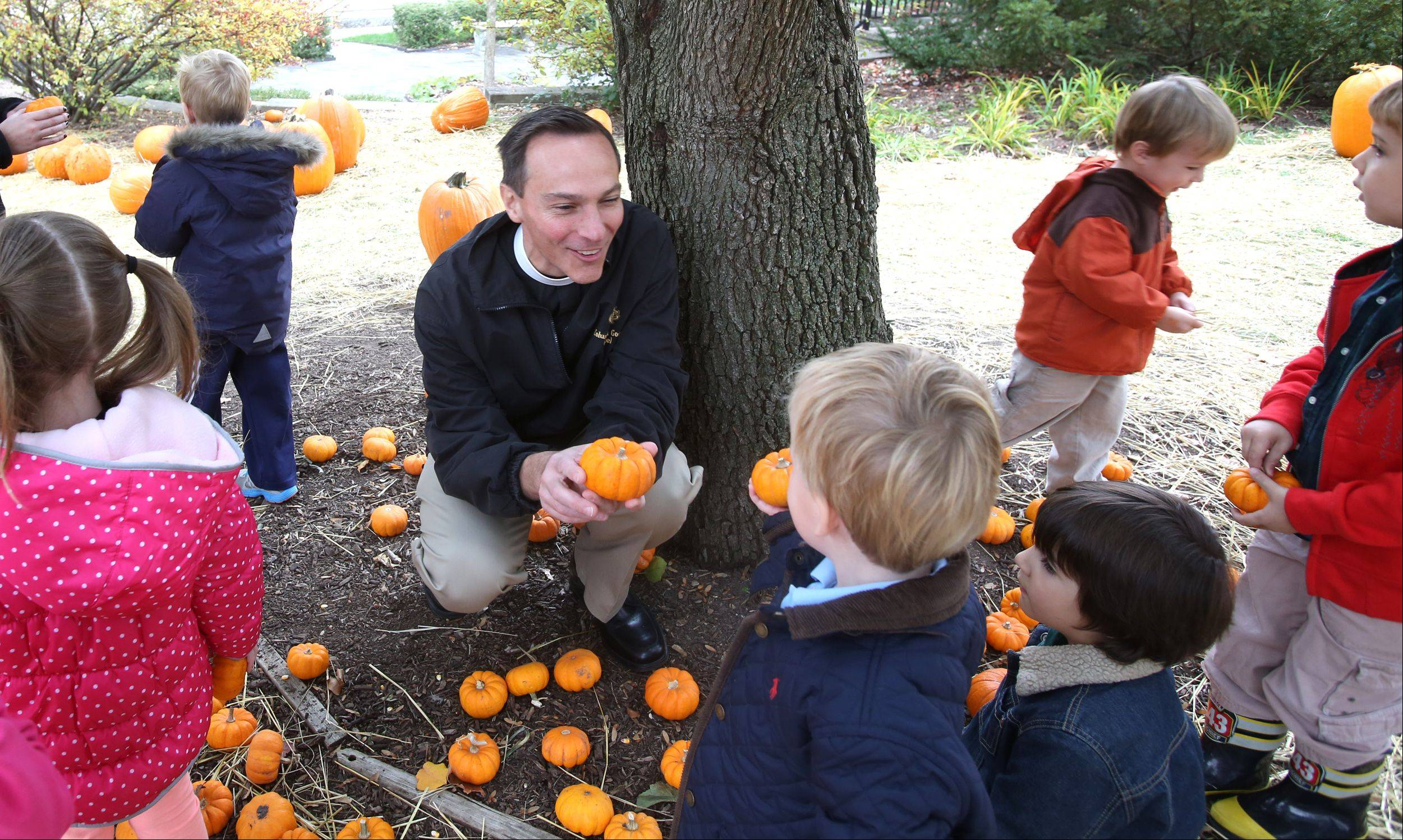 "The Rev. George Smith of St. Mark's Episcopal Church in Glen Ellyn talks with preschoolers in a pumpkin patch on the church grounds. Proceeds from pumpkin sales benefit Public Action to Deliver Shelter, or PADS. This is the seventh year the church has sponsored the pumpkin sale and it usually raises about $5,000. ""Everybody loves pumpkins,"" Smith said. ""This is an outreach program for people in the community to (help) end homelessness in DuPage County."""
