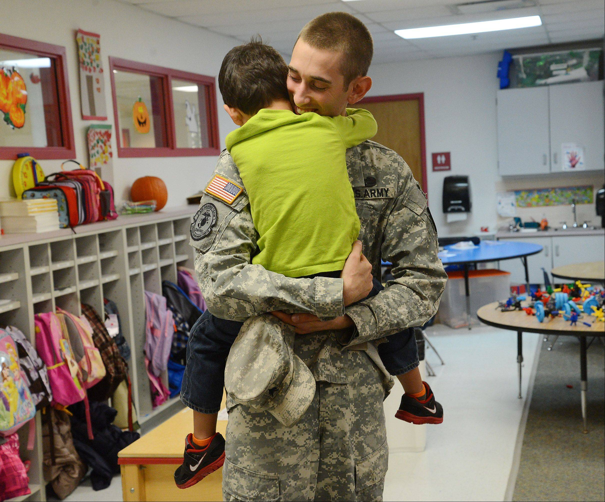 U.S. Army Sgt. Robert Schroeder of Lake Barrington gets a hug from his son, William, on Wednesday when visiting St. Anne Parish School in Barrington. Schroeder planned on surprising the 4-year-old in his pre-Kindergarten class, but instead got a surprise hero's welcome from the school's students and staff.