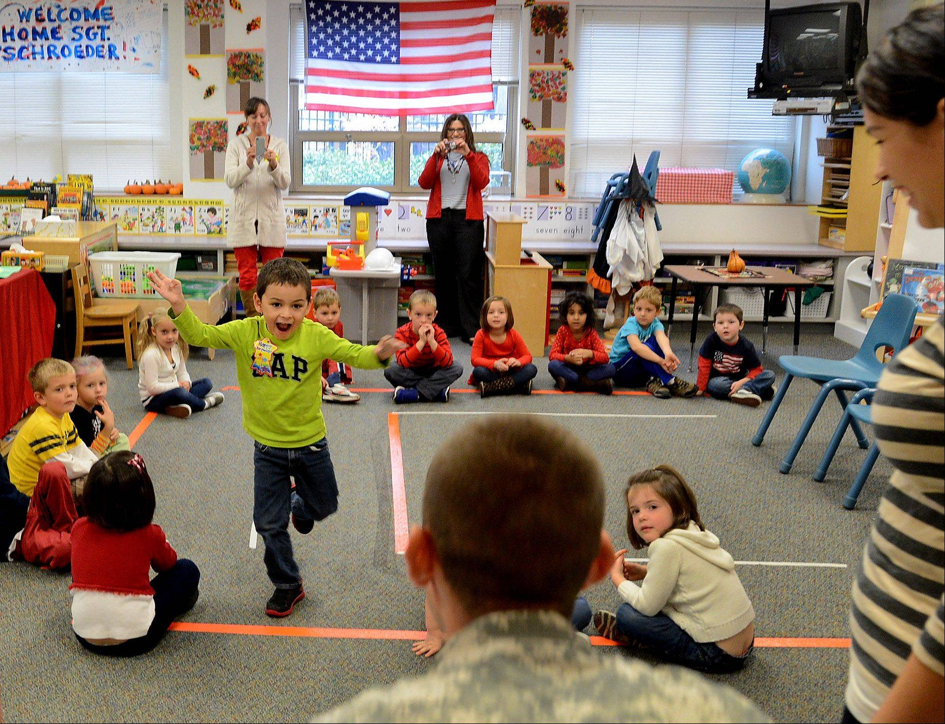 William Schroeder rushes to give his father, U.S. Army Sgt. Robert Schroeder of Lake Barrington, a hug Wednesday in his pre-Kindergarten classroom at St. Anne School in Barrington.