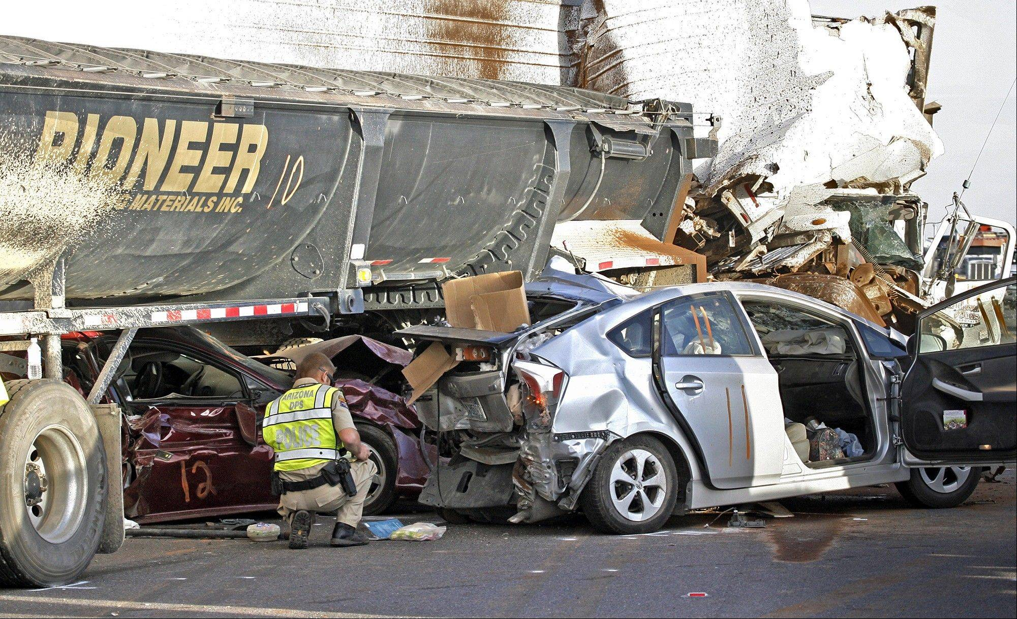 Arizona Department of Public Safety officers investigate a multiple fatality accident involving six semi tractor-trailers and 19 other vehicles in the eastbound lanes of Interstate 10 south of Casa Grande, Ariz., on Tuesday, Oct. 29, 2013. Authorities say three people are dead and at least 12 others injured after a dust storm led to chain-reaction collisions.