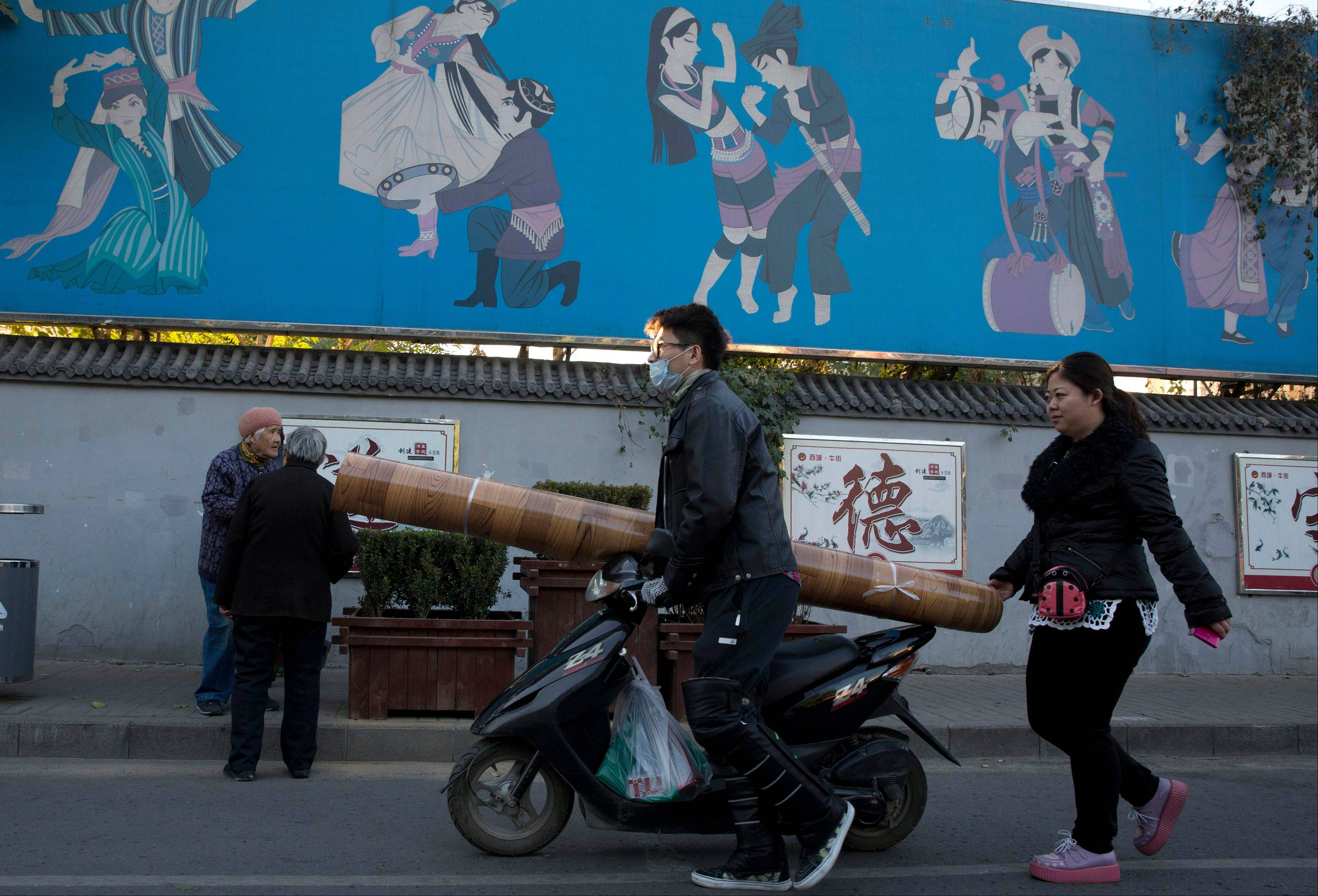 Residents walk by a mural depicting China's ethnic minorities including Uighurs in Beijing, China.