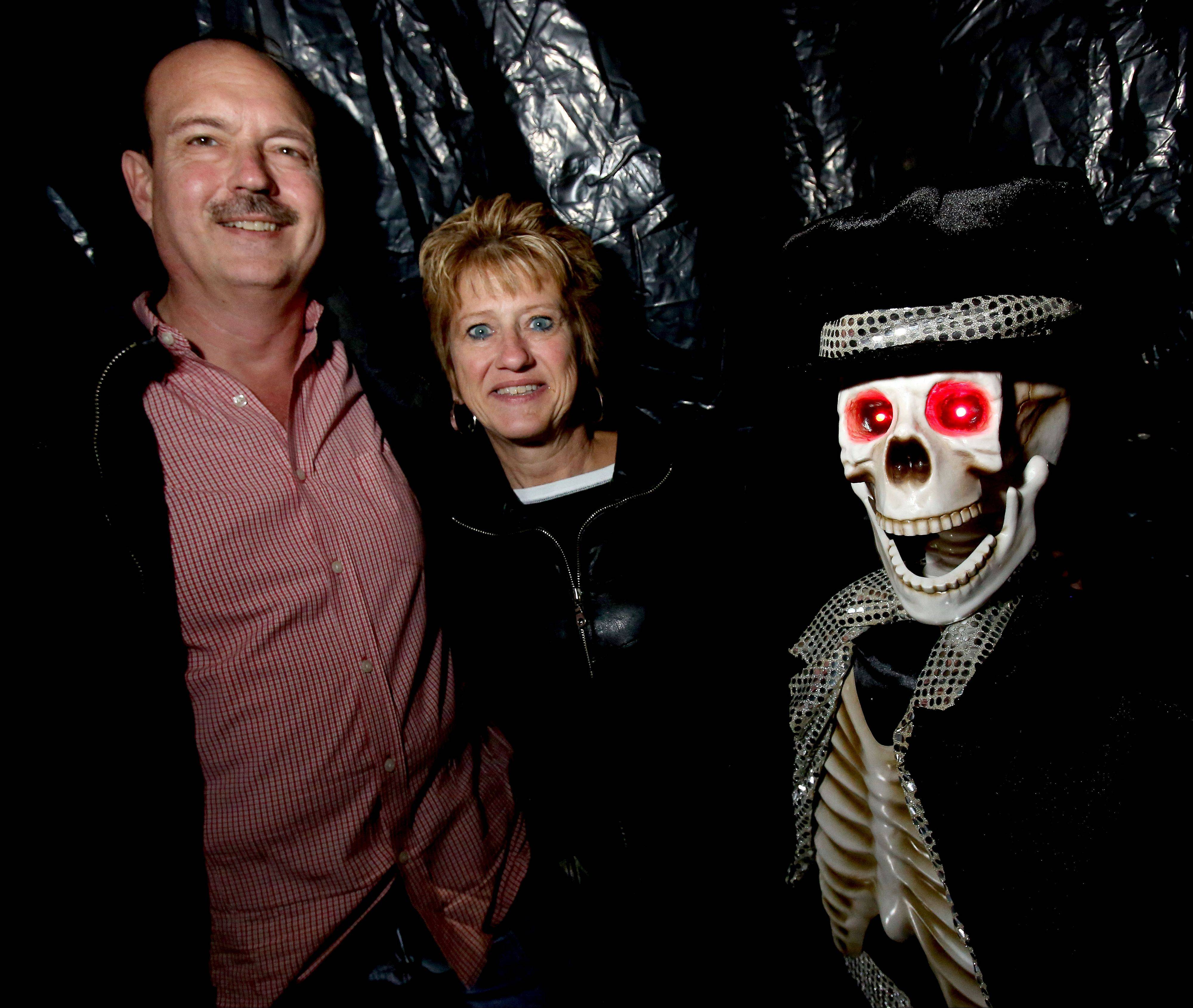 Larry and Liz Hunka with one of the ghouls in their haunted garage in Wheaton, which they will be stopping after 13 years.
