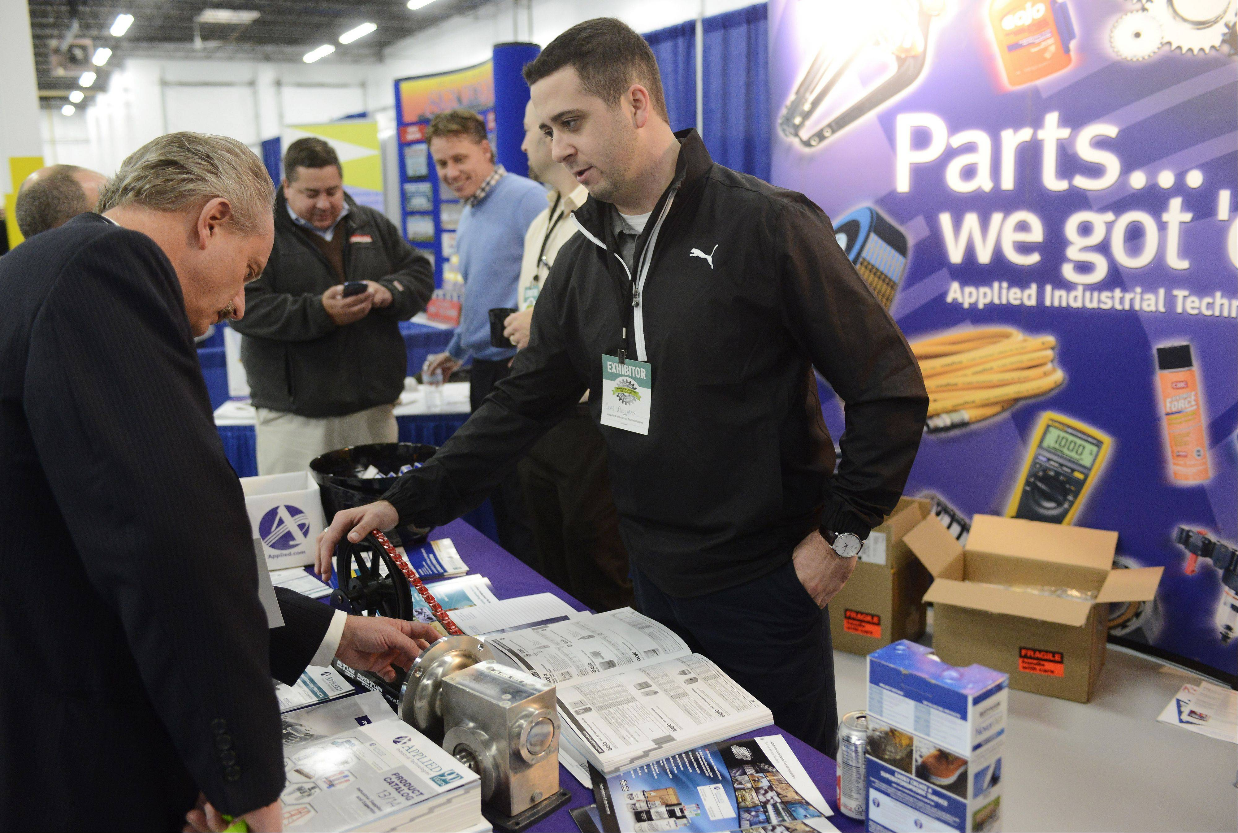 Gregory Godfrey of First American Bank, Addison, chats with Cory Williams of Applied Industrial Technologies while viewing the company's products during the Elk Grove Village business expo Tuesday.
