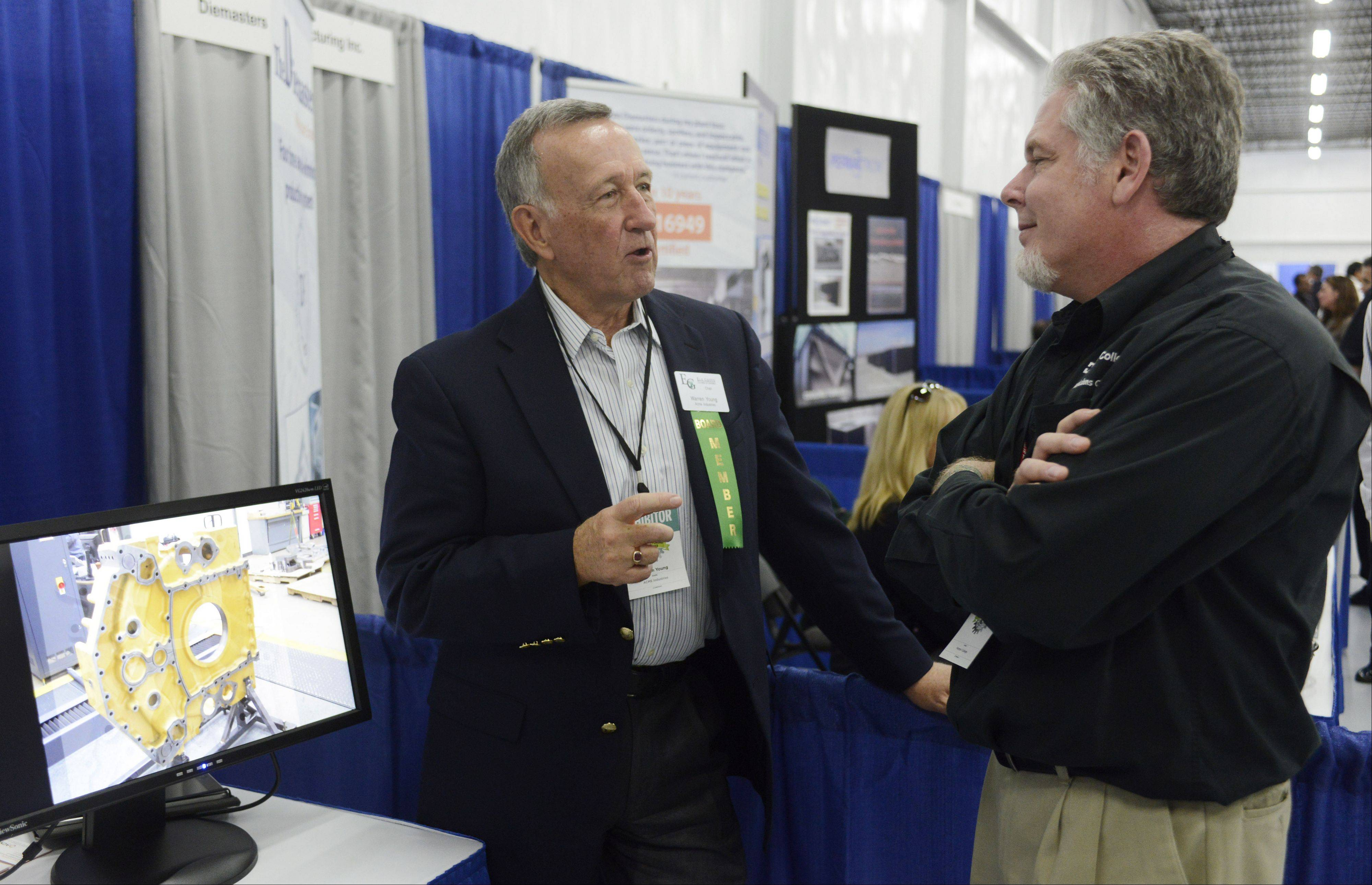 Warren Young, left, of Acme Industries talks with Mark McPherrin of Harper College admissions outreach during the Elk Grove Village business expo Tuesday.