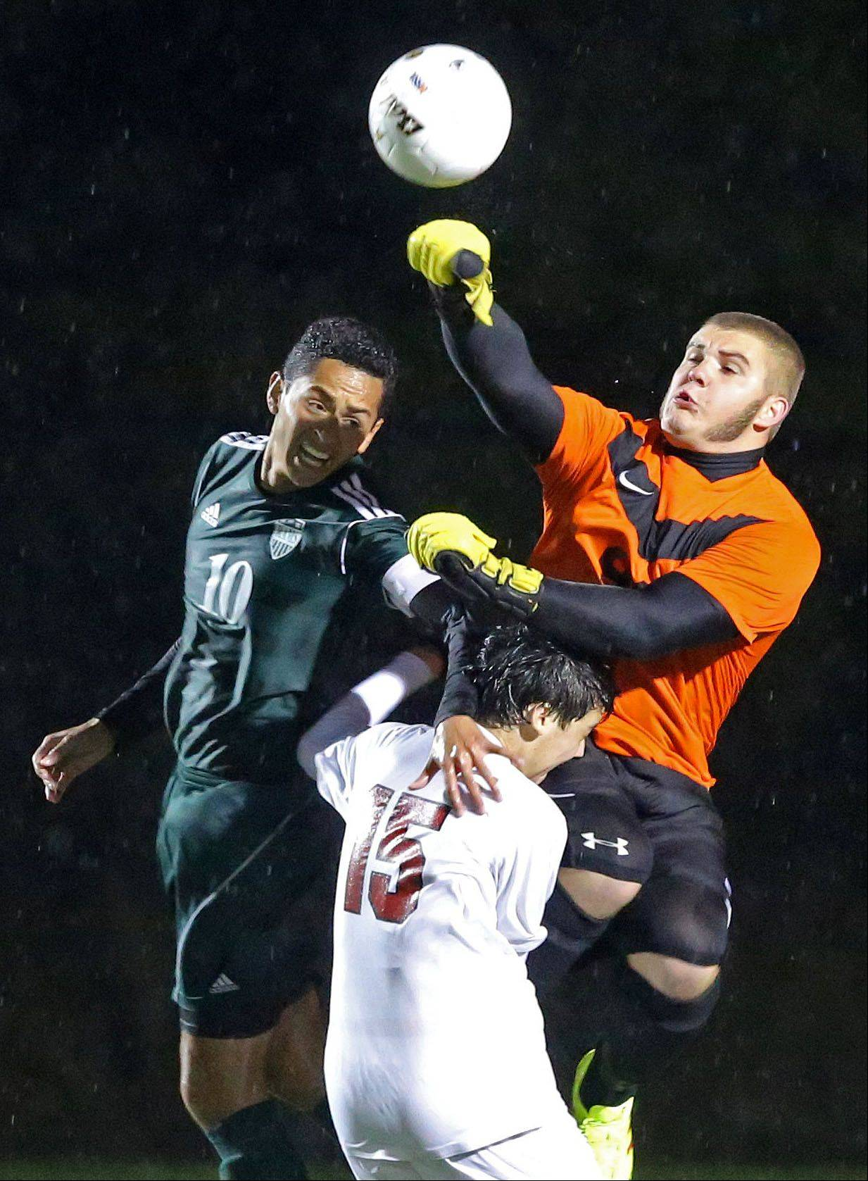Grayslake Central's Johnny Madrid, left, and Antioch's Jordan Keller (15) and Tommy Tritschler go up for a ball during their Class 3A sectional semifinal Wednesday at Grayslake North High School.