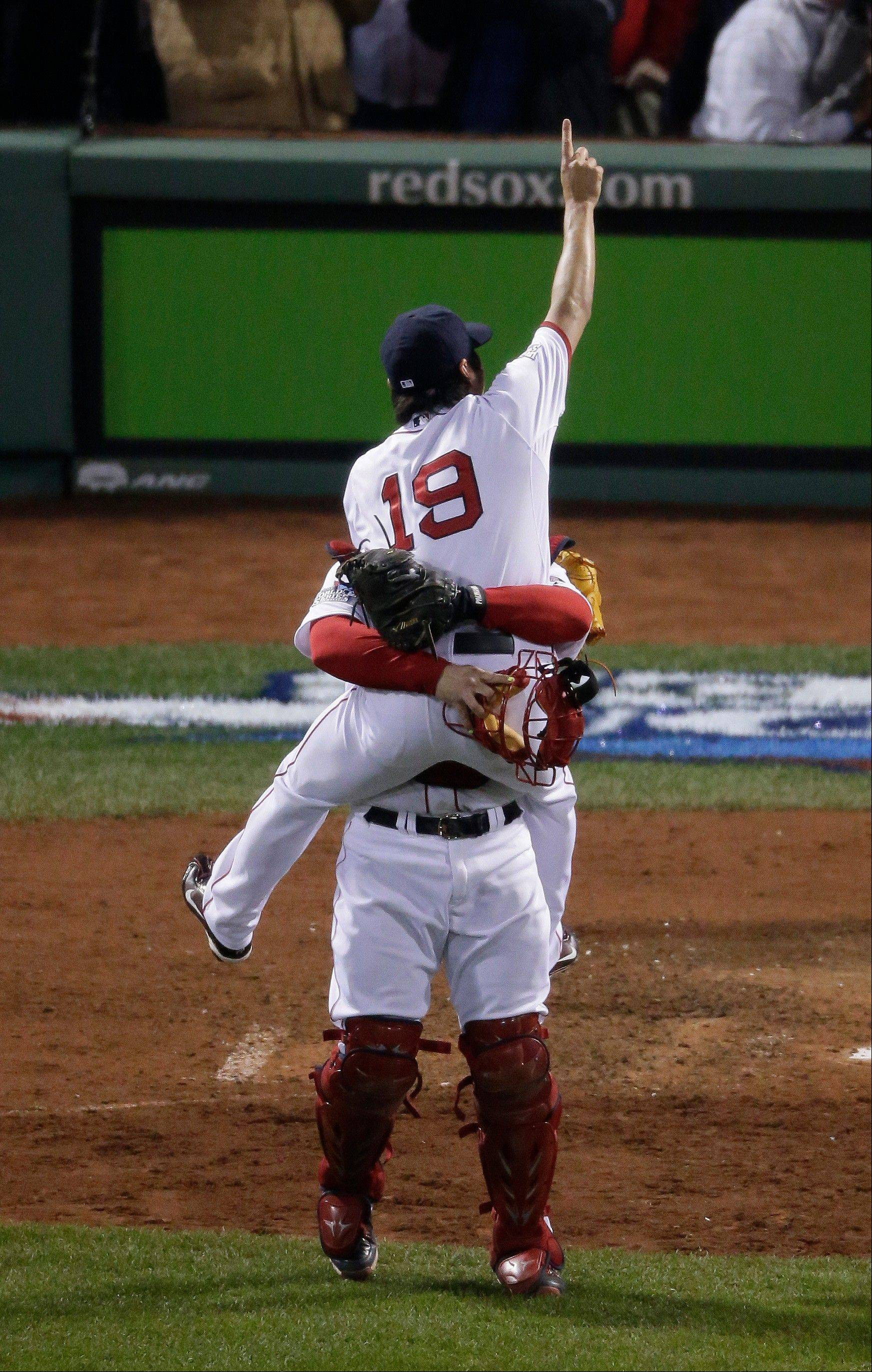 Boston Red Sox relief pitcher Koji Uehara (19) and catcher David Ross celebrate after Boston defeated the St. Louis Cardinals in Game 6 of baseball's World Series Wednesday, Oct. 30, 2013, in Boston. The Red Sox won 6-1 to win the series.