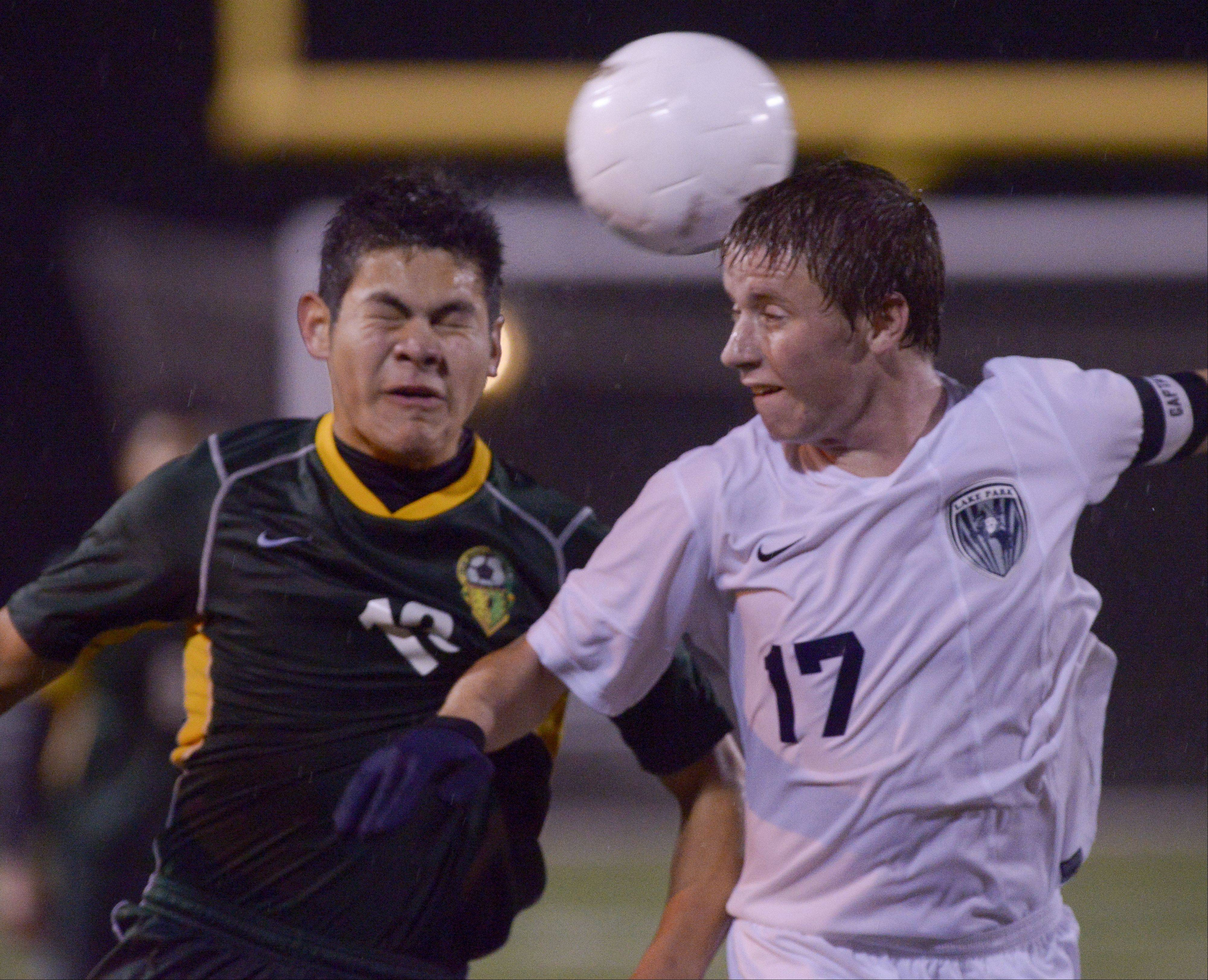 Arnold Aguilar of Elk Grove and Joe Keane of Lake Park battle for control of the ball during in the Class 3A Schaumburg sectional semifinals Wednesday.