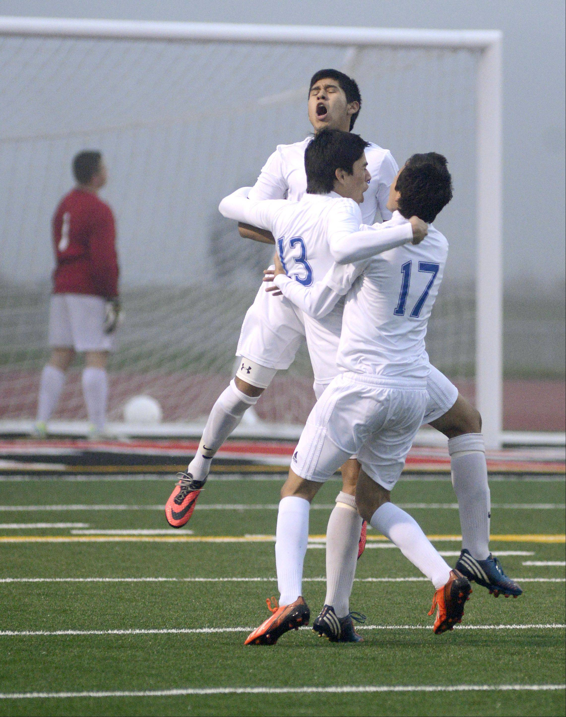 Larkin's Hector Mendoza (13) is congratulated by teammates Gonsalo Garcia, left, and Fredy Jungo after scoring the first goal for the Royals in the first half as Hononegah goalie Henry Reynolds stands in the net at the Huntley sectional semifinals on Wednesday.